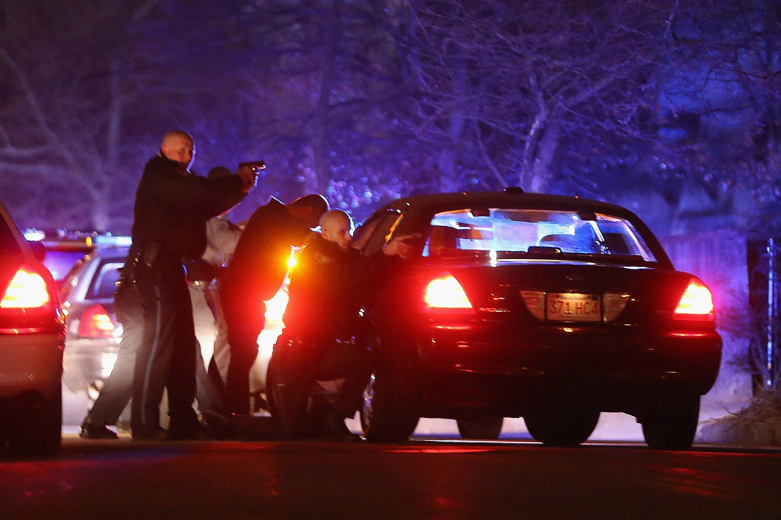 Image: Police with guns drawn search for a suspect in Watertown, Mass.