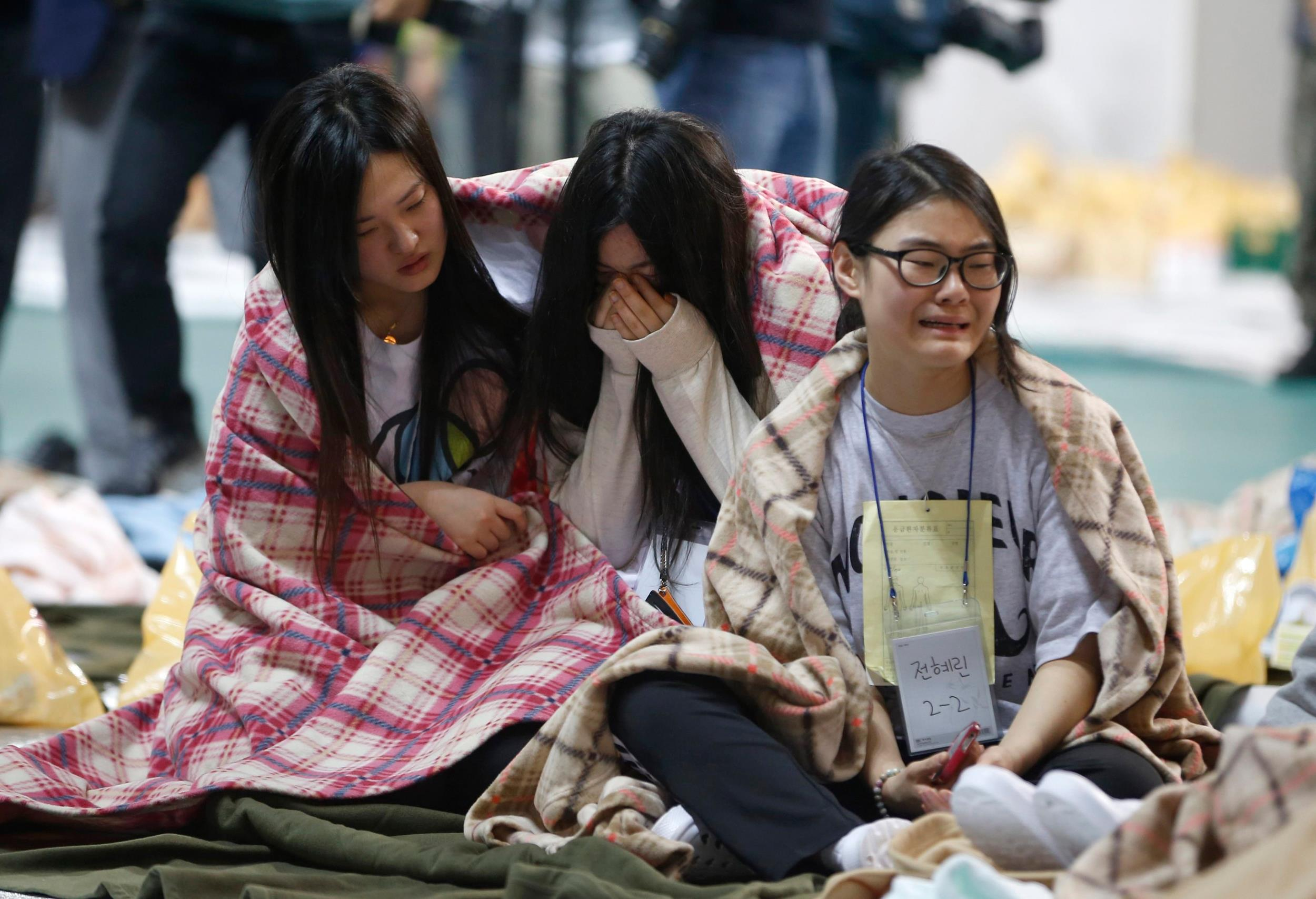 Image: Rescued passengers cry at a gym where rescued passengers gather in Jindo