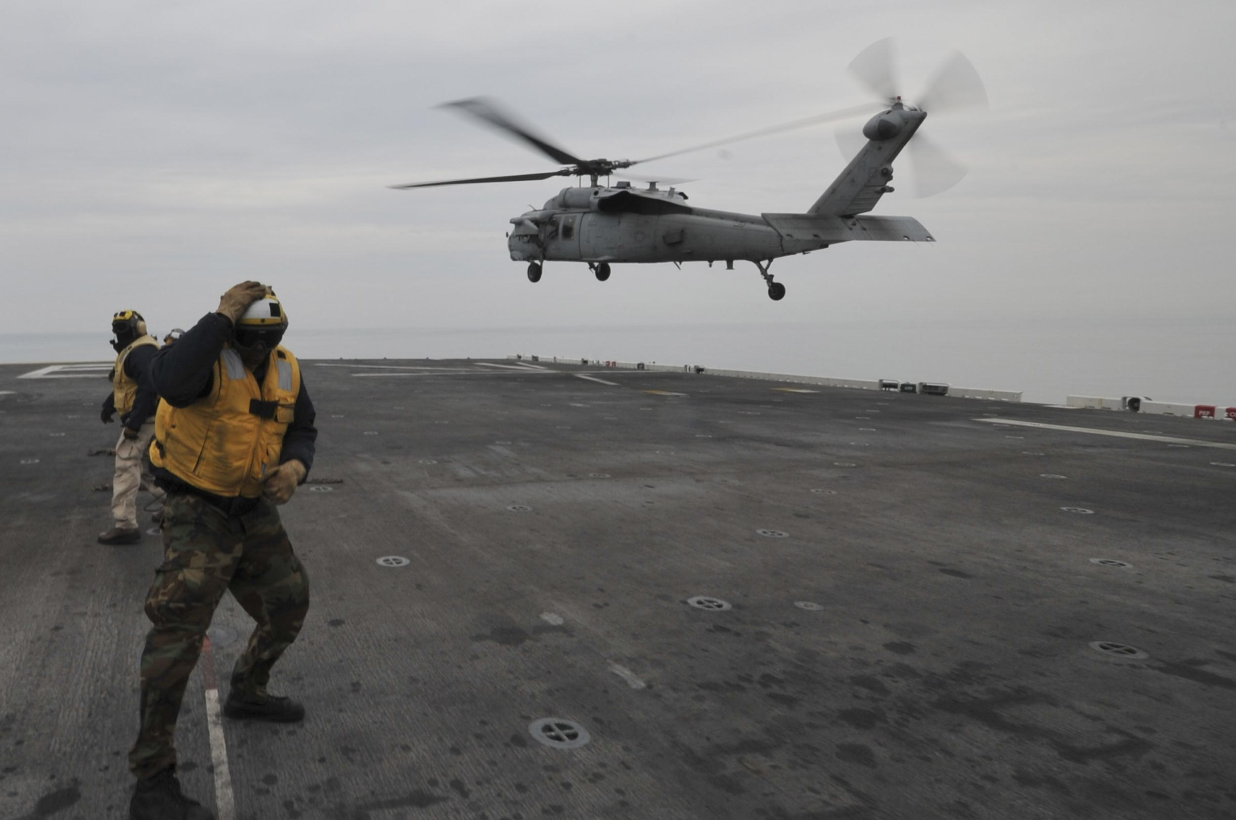An MH-60S Sea Hawk helicopter lands on the flight deck of the forward-deployed amphibious assault ship USS Bonhomme Richard