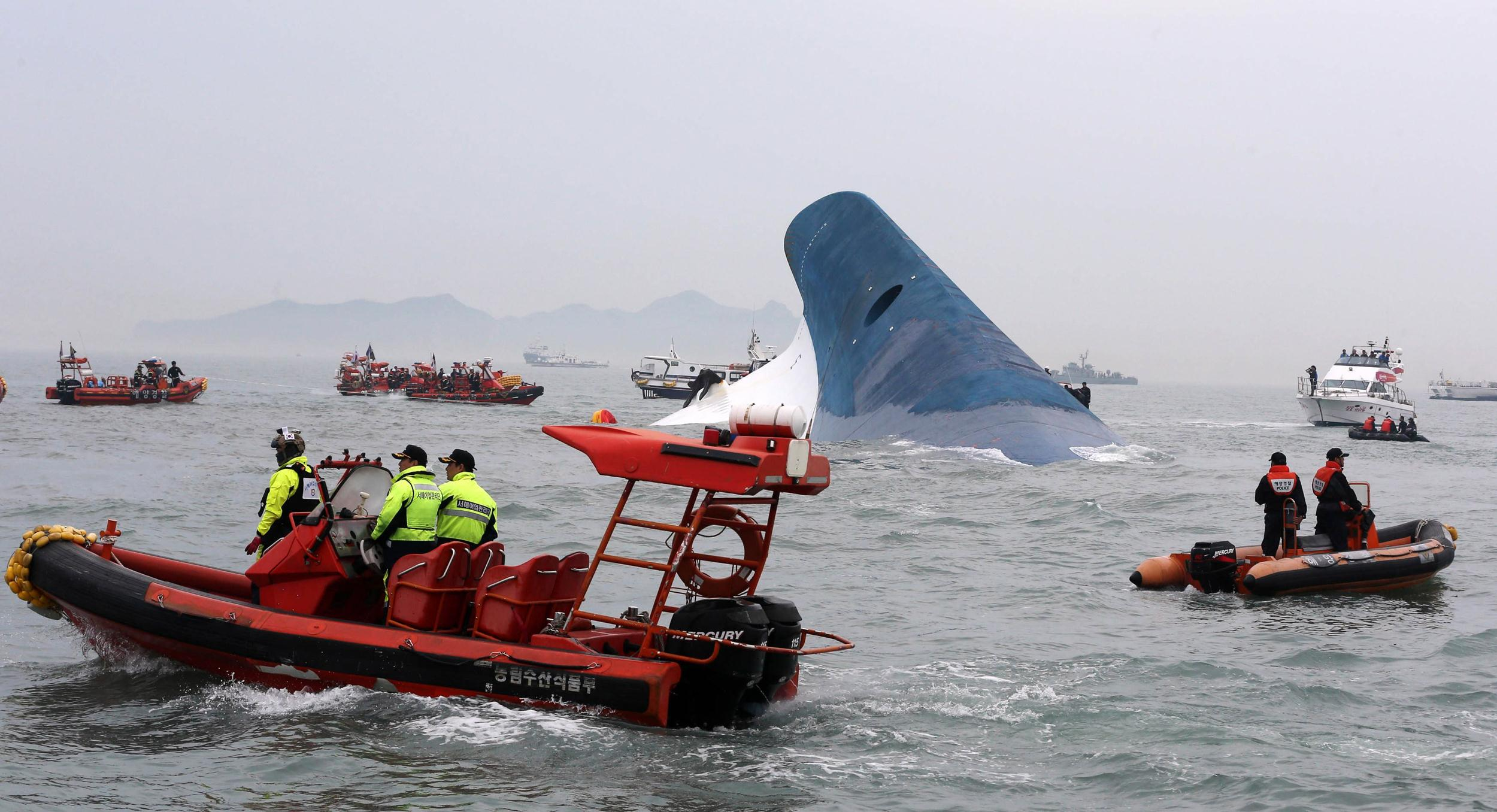 Image: South Korean maritime policemen search for passengers in the sea around the sinking ferry Sewol