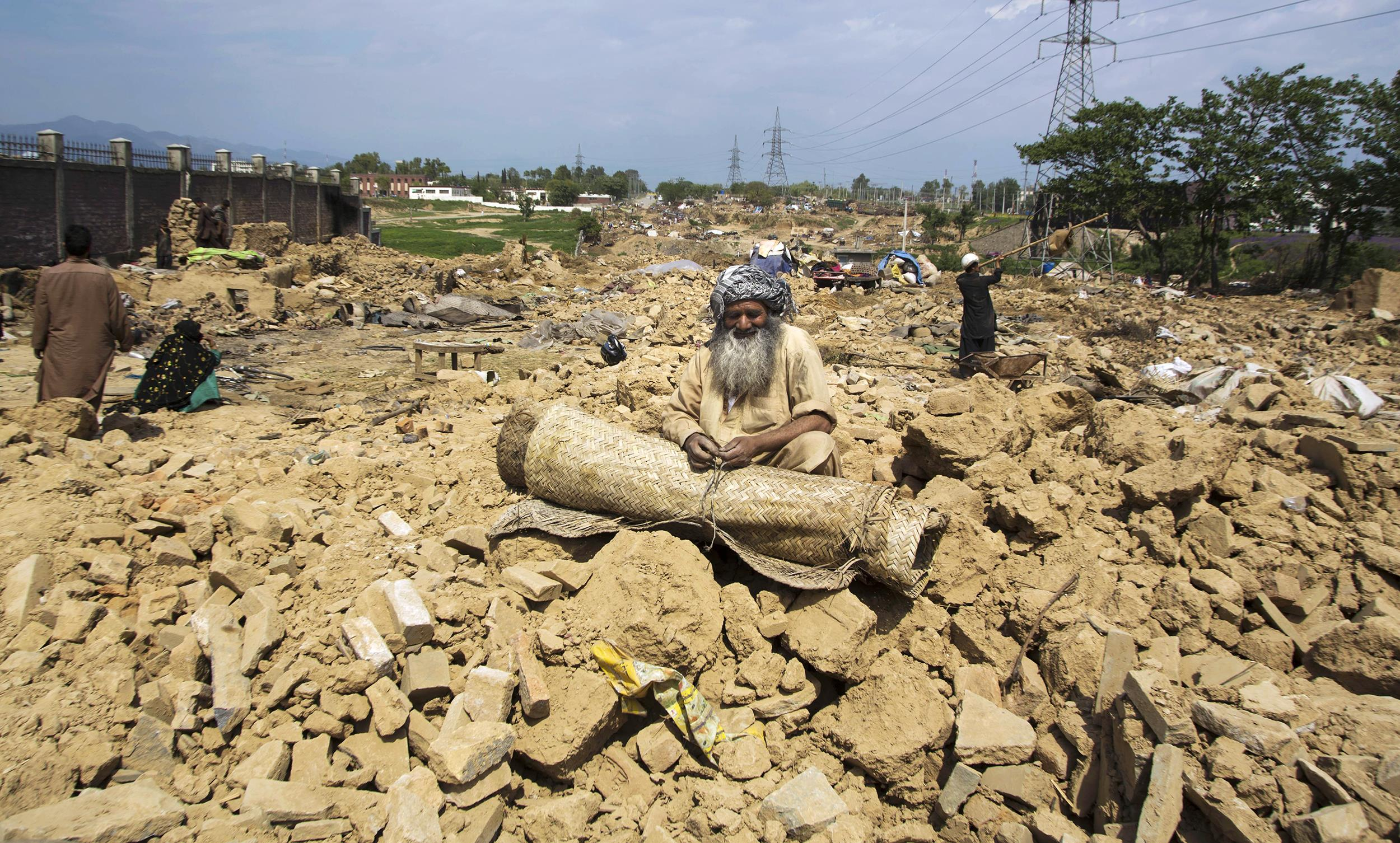 Image: Afghan refugee Saboor Khan collects his belongings after authorities razed his house in the slums of Islamabad