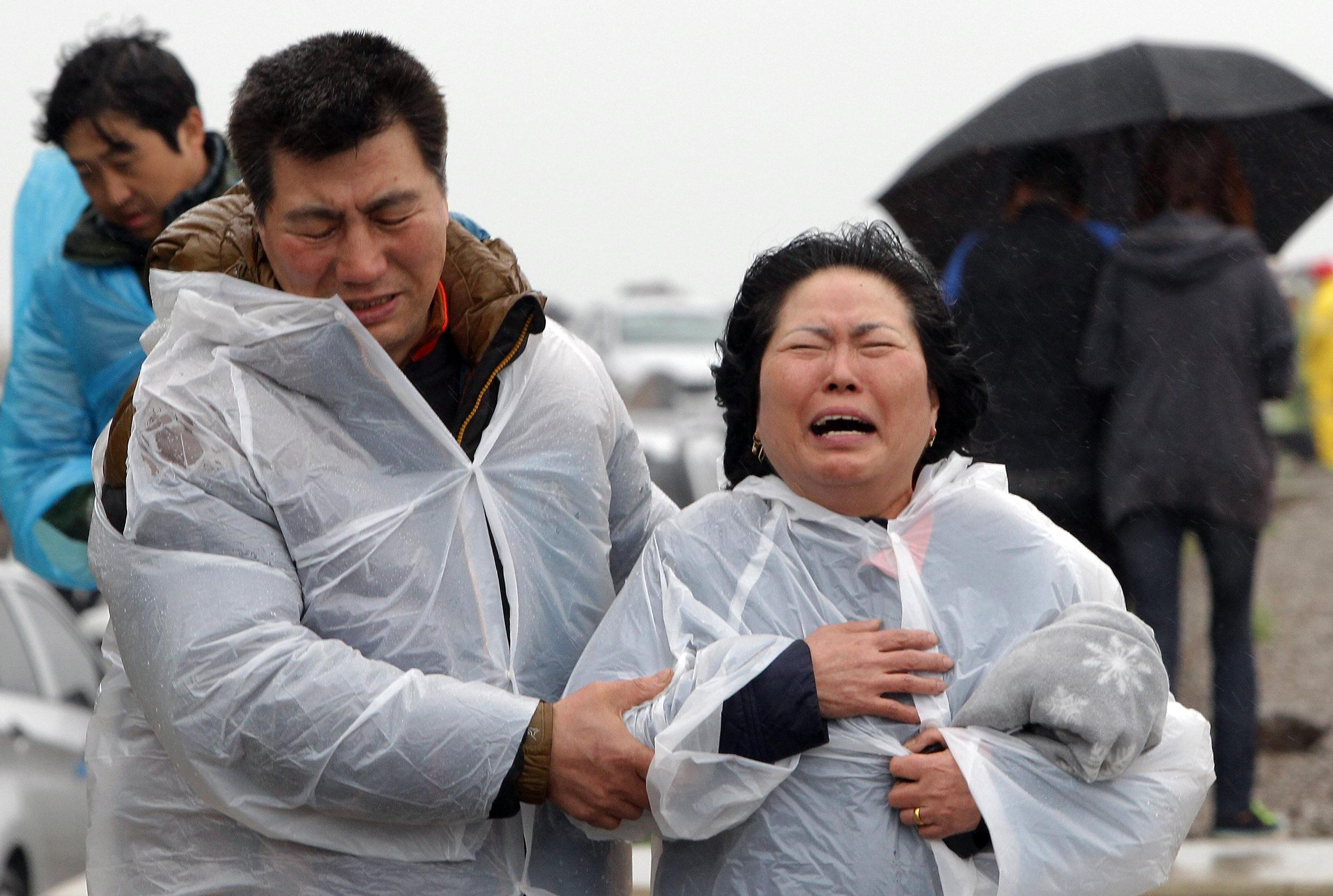 Image: A relative weeps as she waits for missing passengers of a sunken ferry