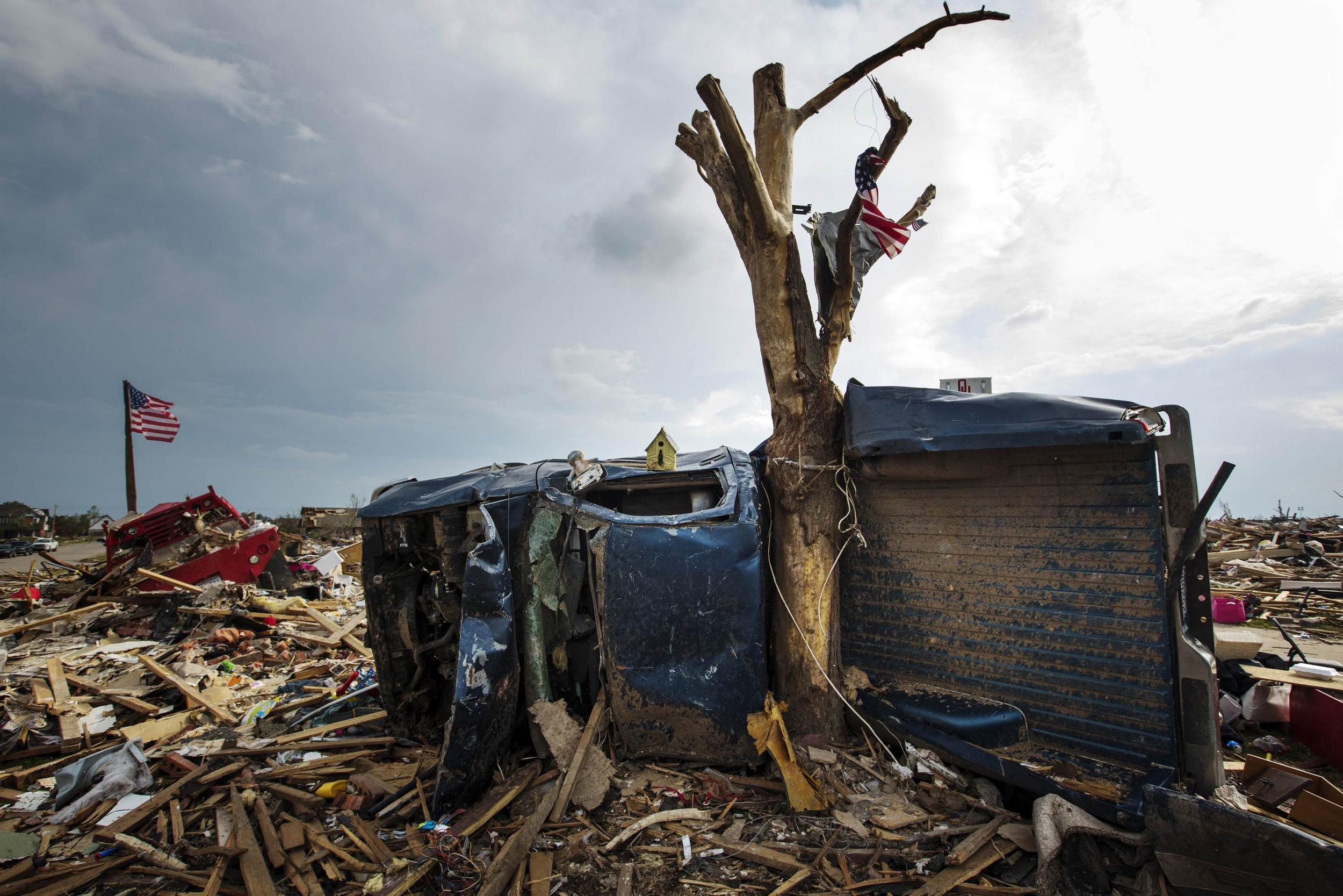 Image: The body of a pickup truck is wrapped around a tree trunk after being thrown there by by a tornado in Moore, Oklahoma in this file photo