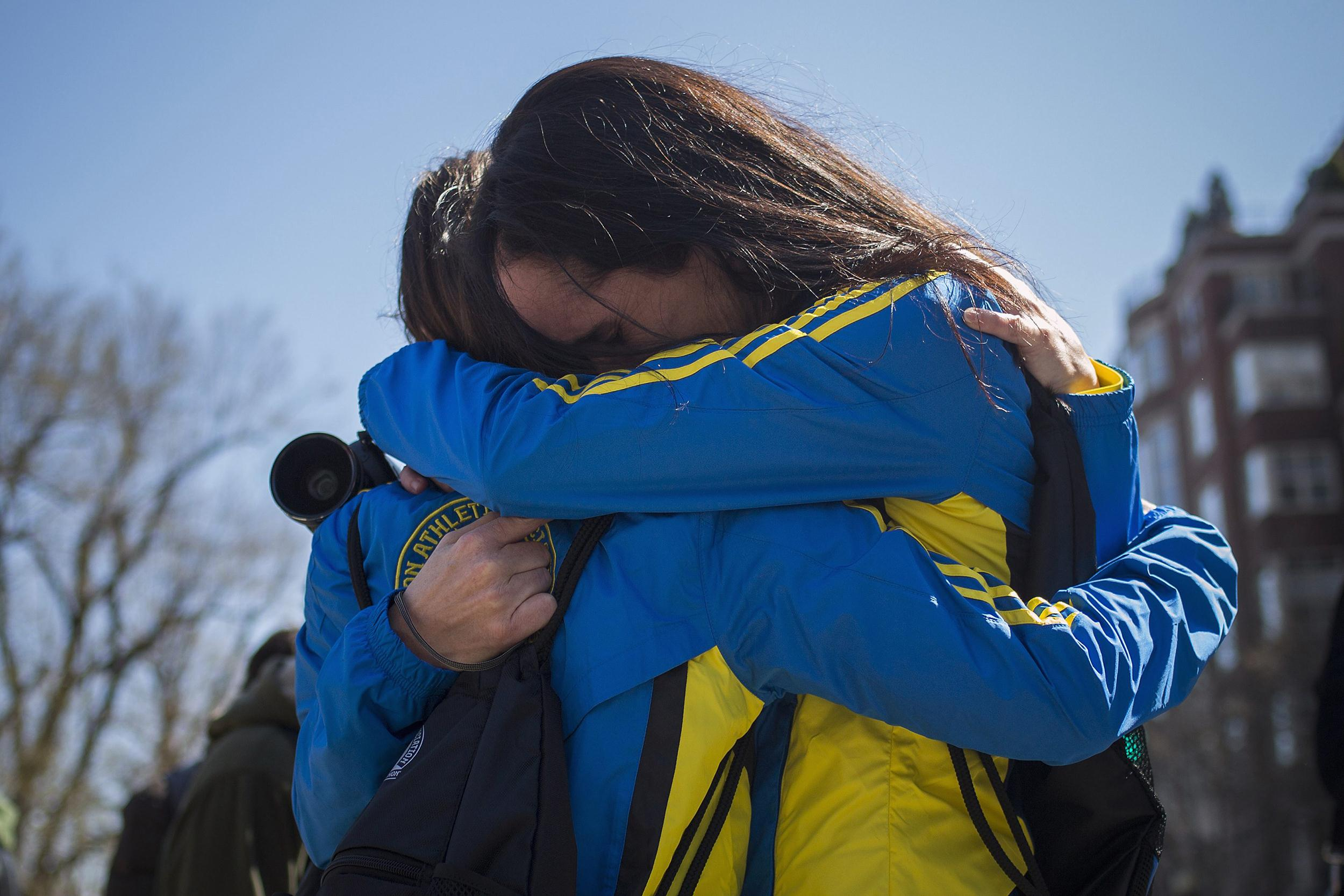 Image: Boston Marathon runners Kresky-Griffin and Snyder embrace at the barricaded entrance at Boylston Street near the finish line of the Boston Marathon in Boston, Massachusetts