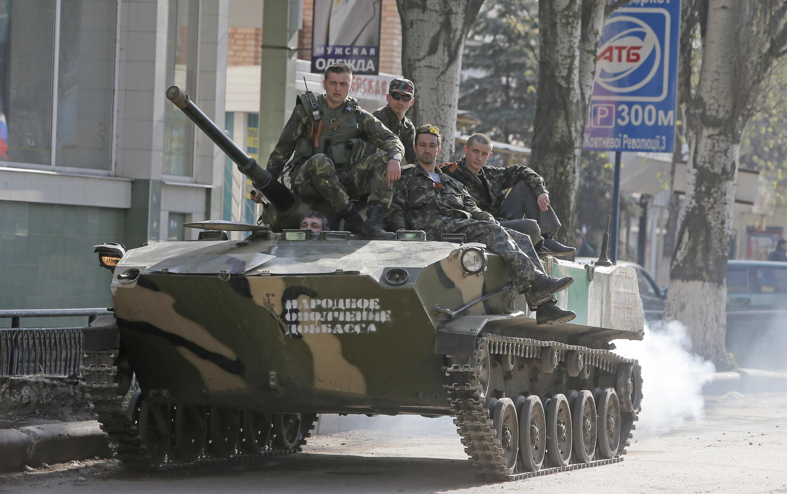 Image: A combat vehicle with pro-Russian gunman on top runs through downtown Slovyansk, eastern Ukraine, on Friday.
