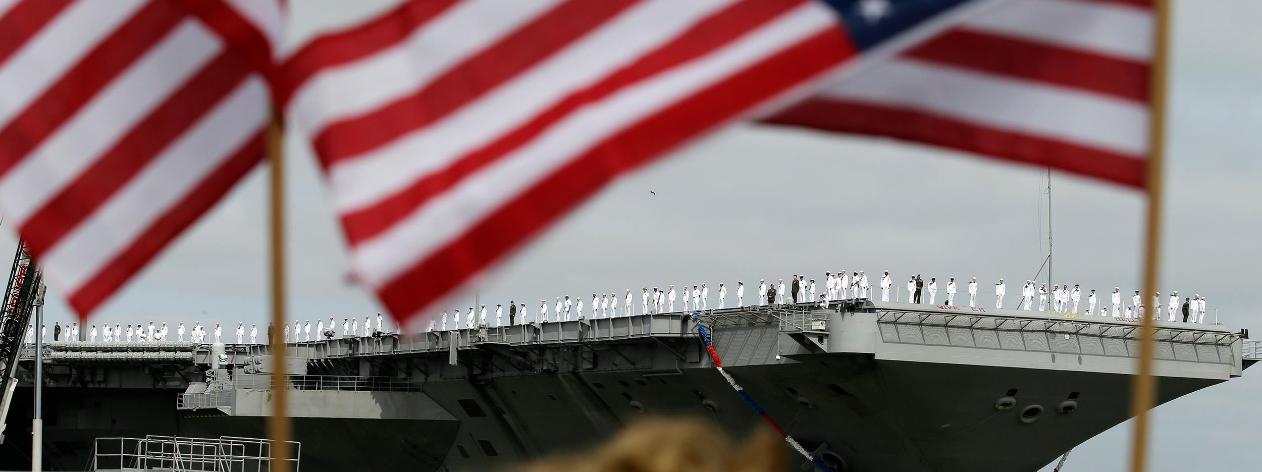 Image: Sailors man the rails as the nuclear aircraft carrier Harry S. Truman approaches the pier at Naval Station Norfolk in Norfolk, Va.