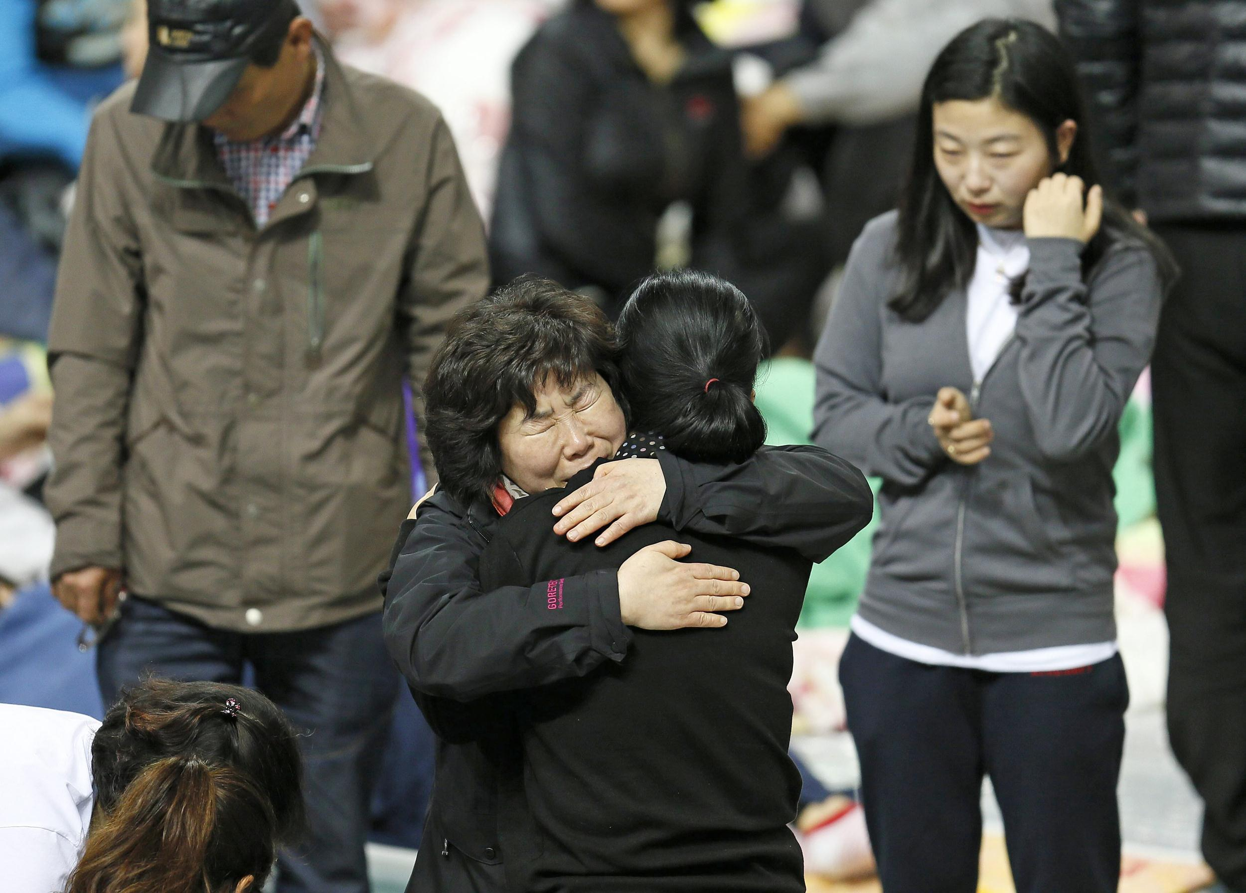 Image: Family members of missing passengers of the Sewol ferry comfort each other Saturday as they wait news about their missing relatives at a gym in Jindo, South Korea.