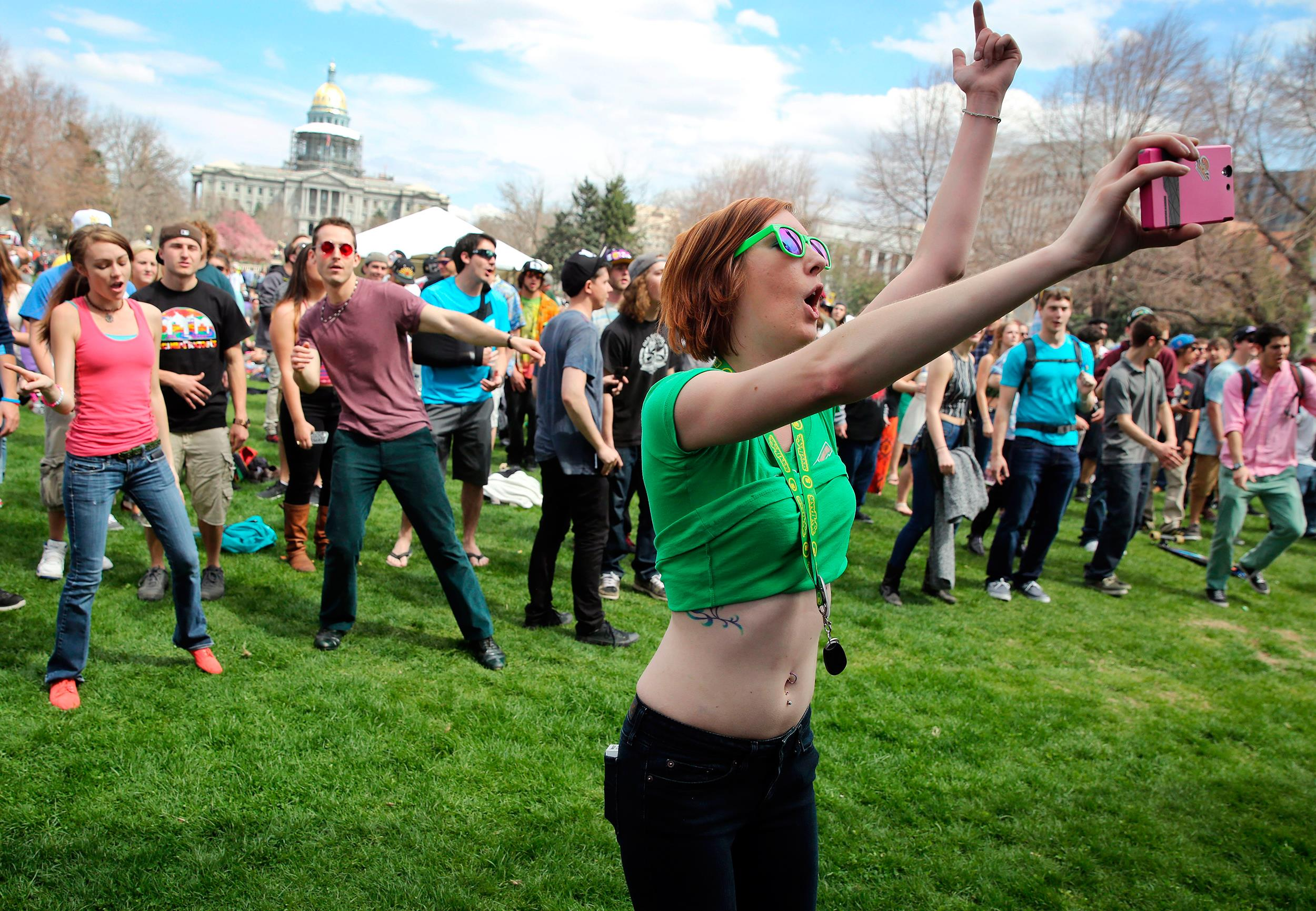 Image: Party goers dance at the annual 4/20 marijuana festival near downtown Denver at Civic Center Park