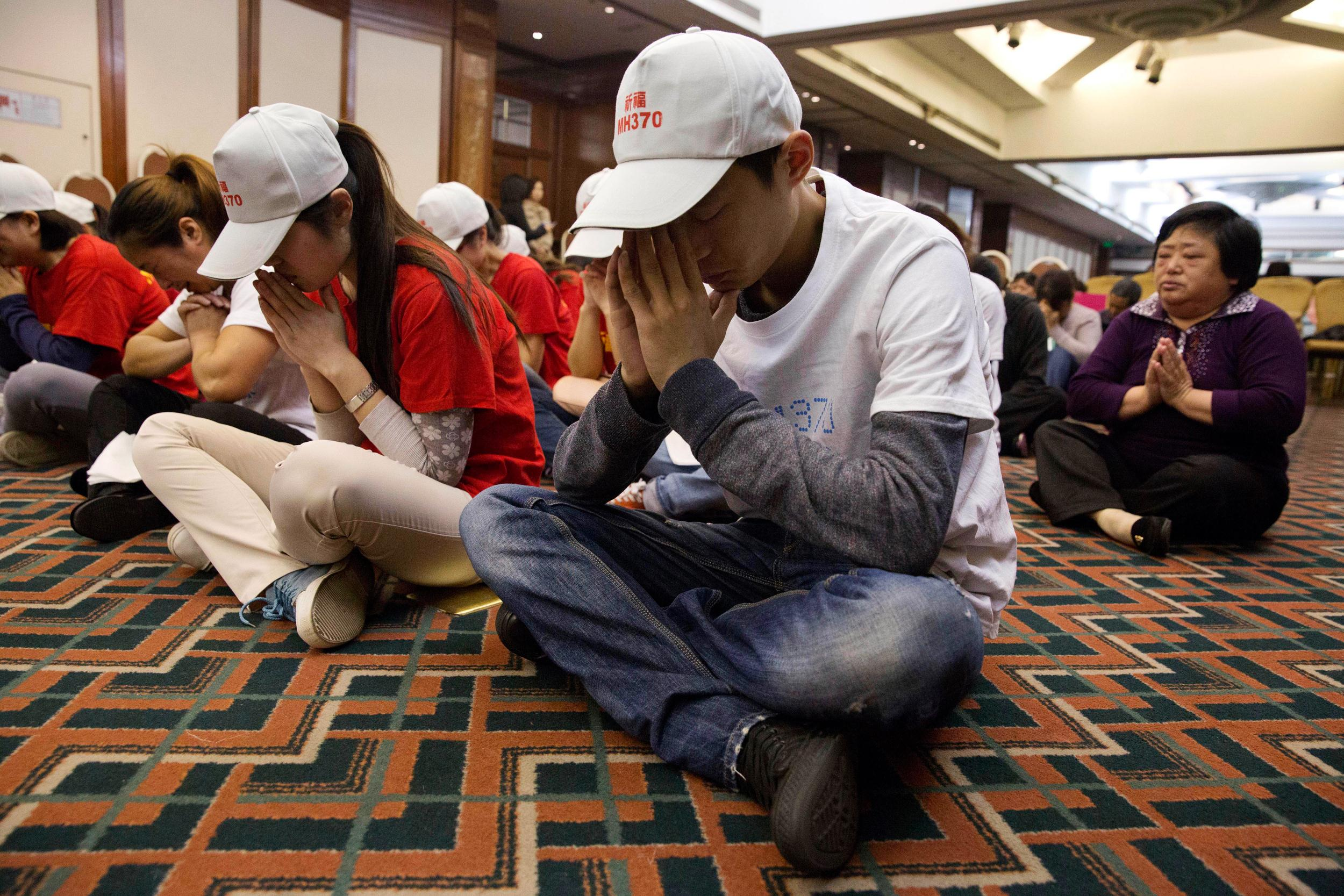 Image: Relatives of Chinese passengers on board the Malaysia Airlines Flight 370 pray at a hotel conference room in Beijing