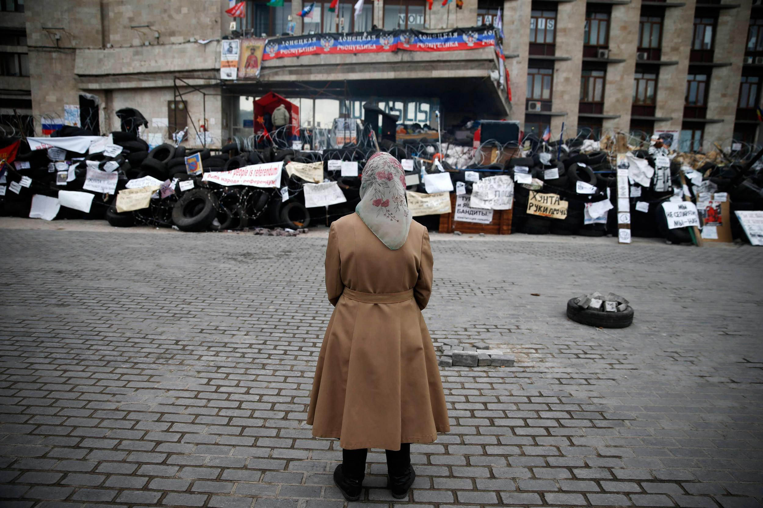 Image: Woman stands in front of a barricade outside a regional government building in Donetsk