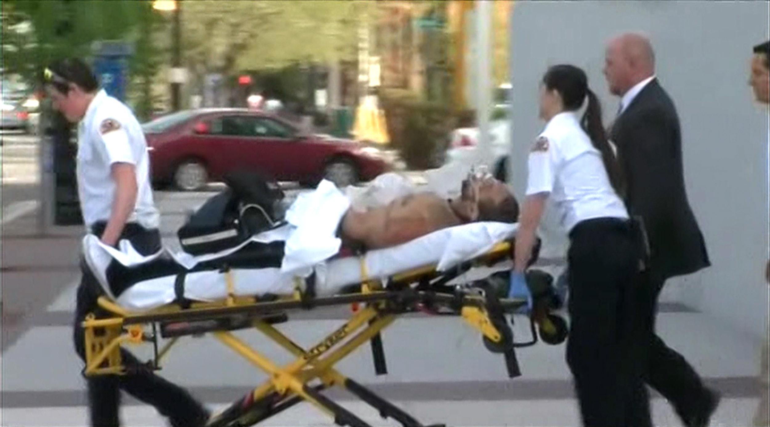 Image: An injured man is wheeled to an ambulance following a shooting at the new Fereral Courthouse in Salt Lake City, Utah.