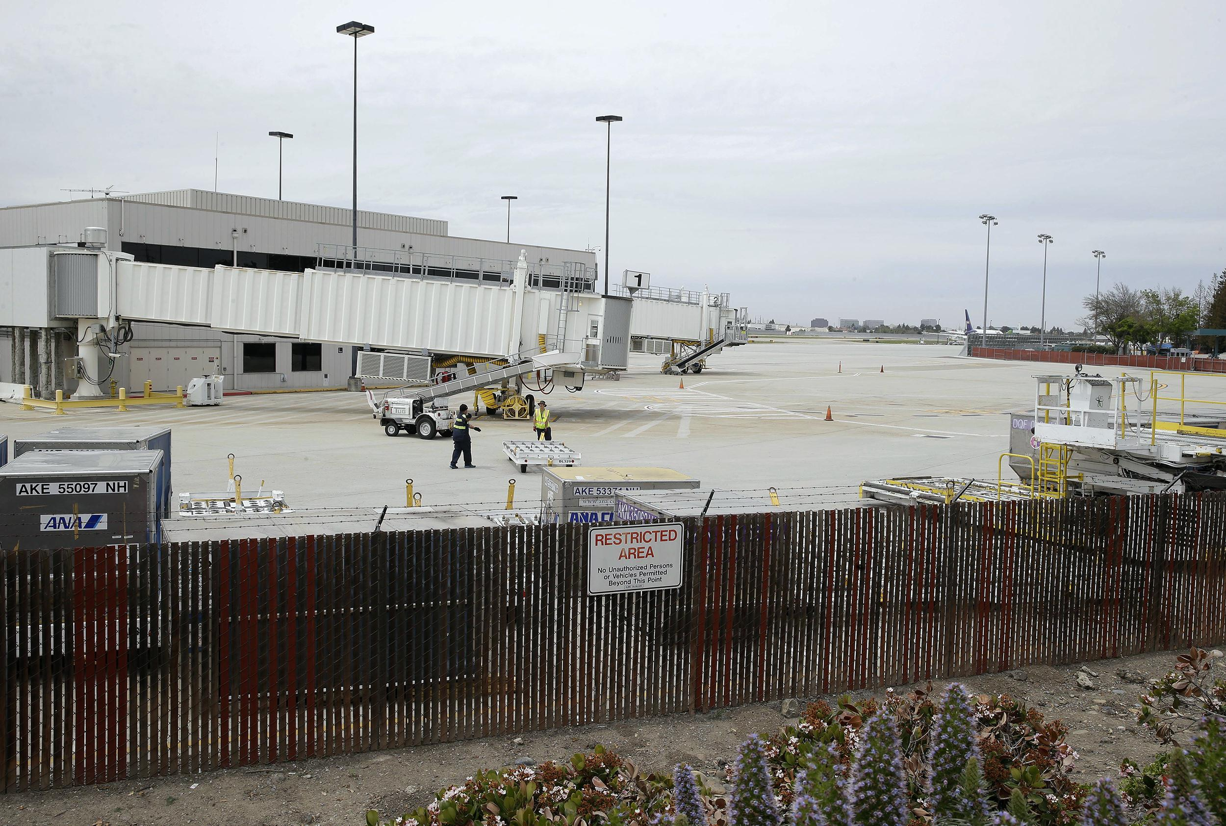 Image:  Workers move equipment near gates used by Hawaiian Airlines at Terminal A of Mineta San Jose International Airport  in San Jose, Calif where  a 16-year-old boy scrambled over a fence at the airport, crossed a tarmac and climbed i