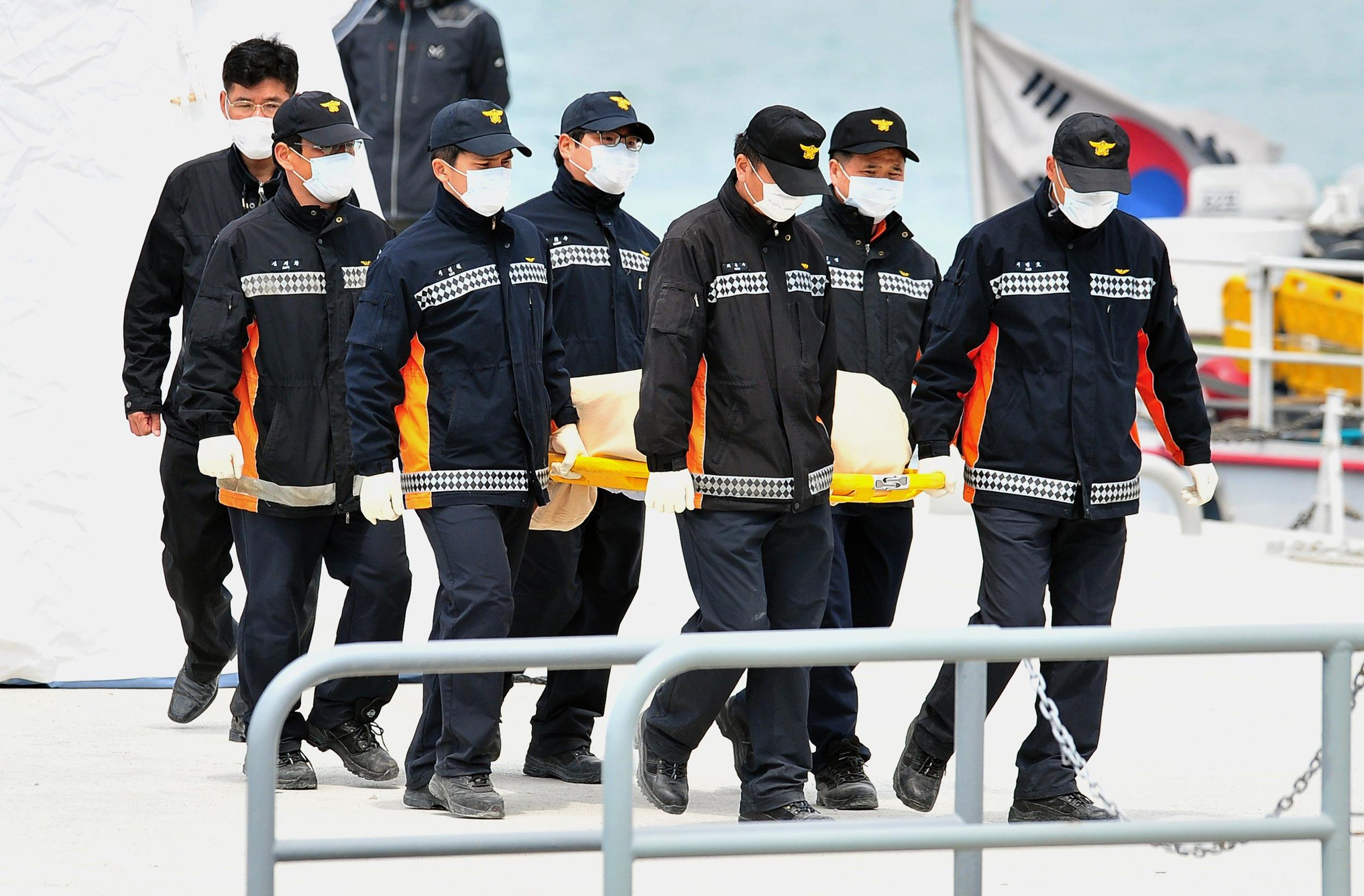 Image: Rescue team members carry the body of a victim recovered from the Sewol ferry