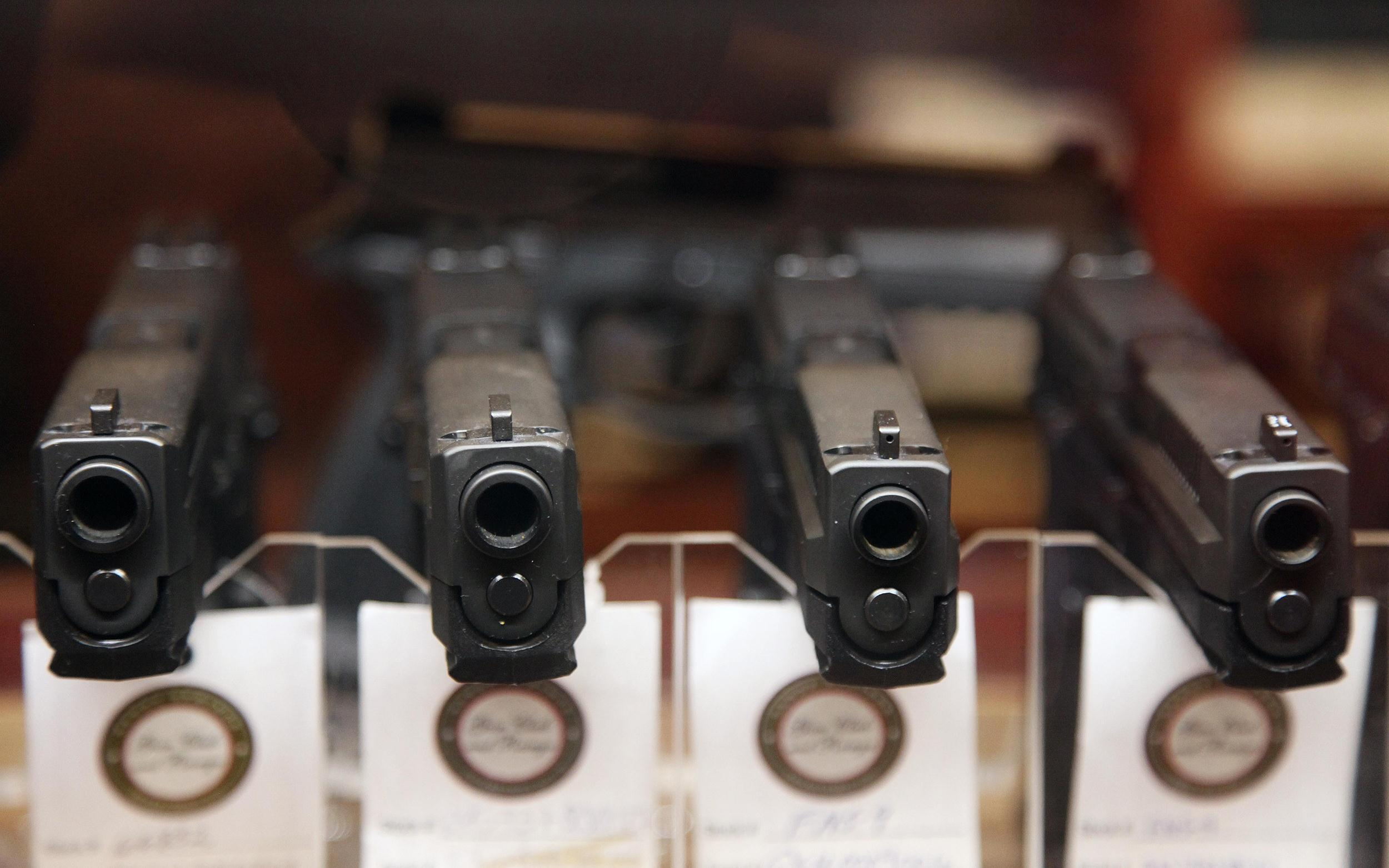 Image: Handguns are displayed in the sales area of a gun club.