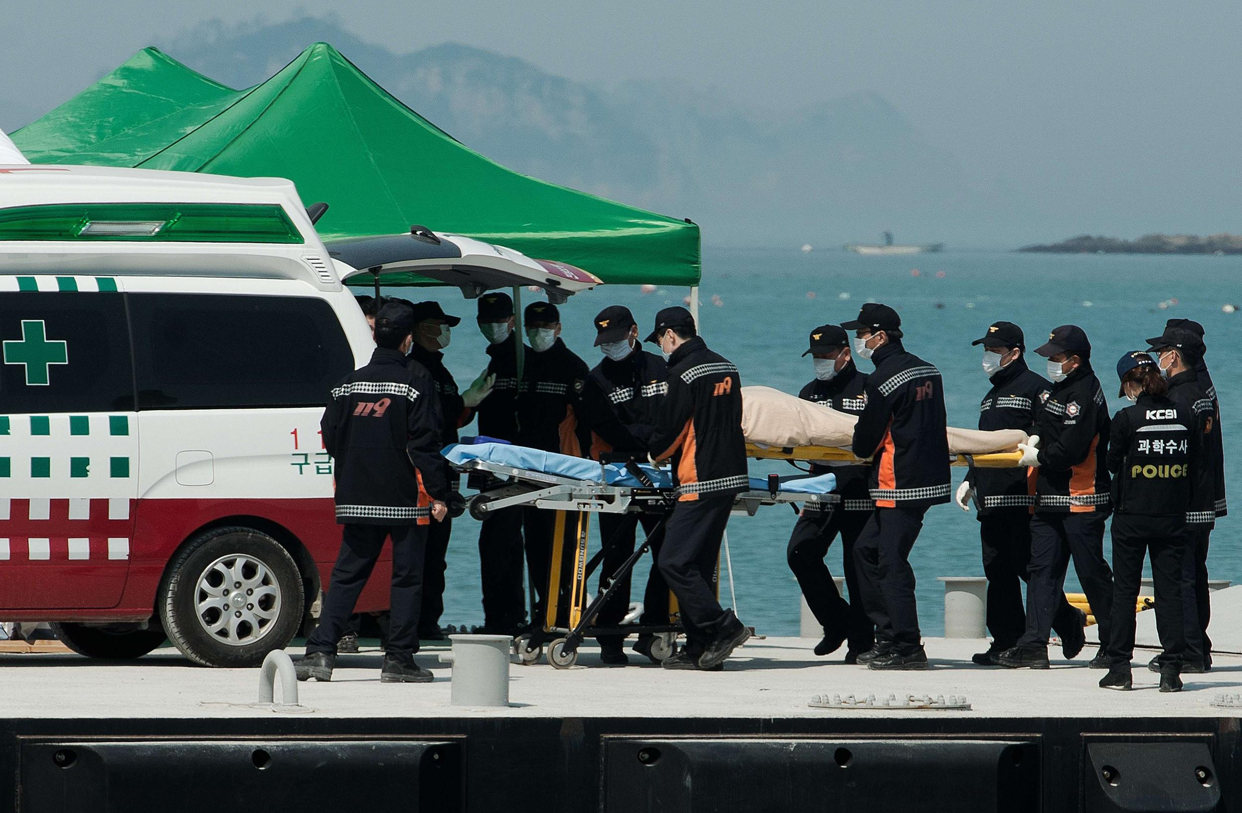 Image: South Korean rescue team members carry the body of a victim recovered from the Sewol ferry