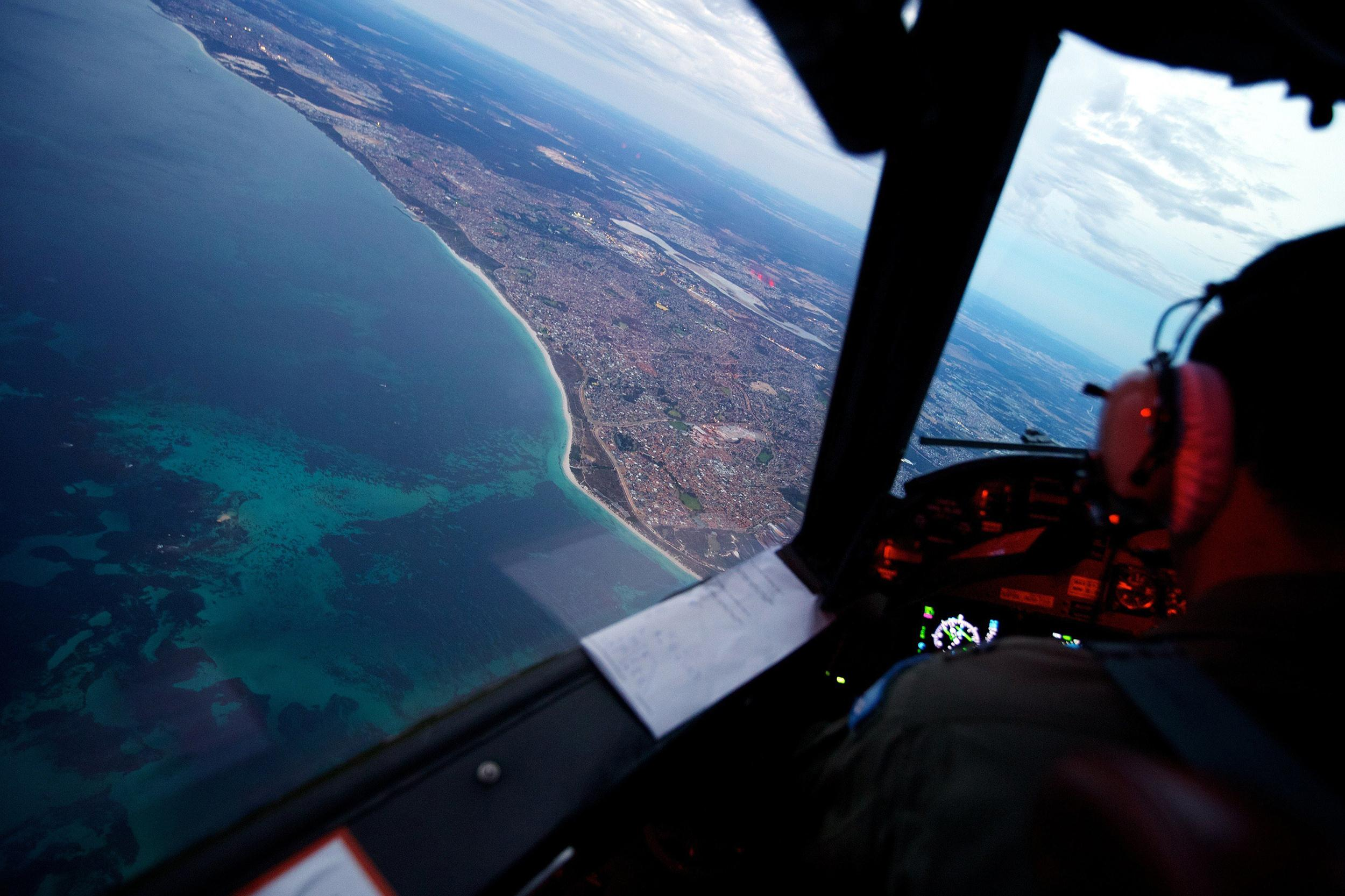 Image: Crew members on board an RAAF AP-3C Orion crossing the coast of Perth