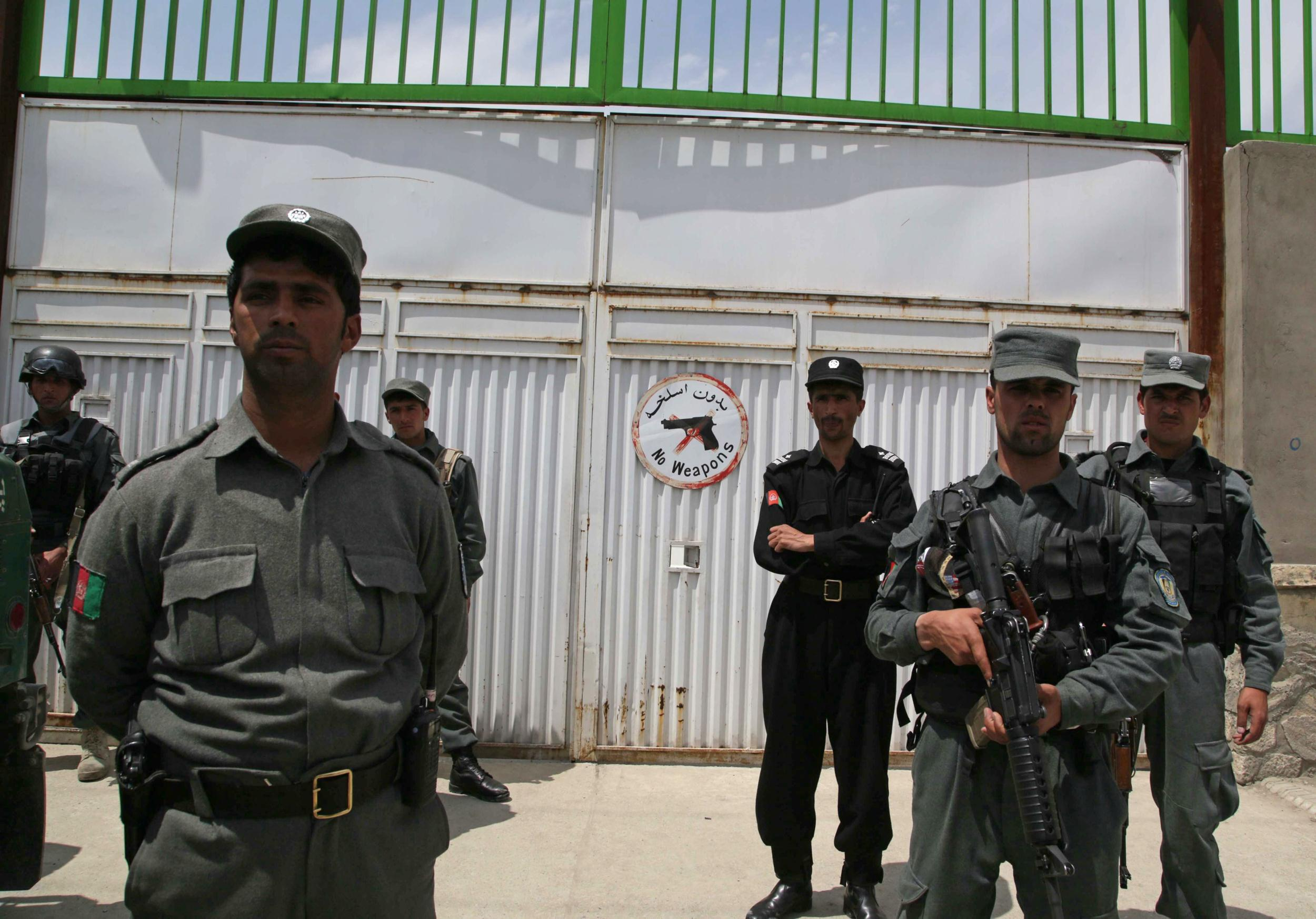 Image: Afghan security officials stand guard outside the Cure hospital in Kabul