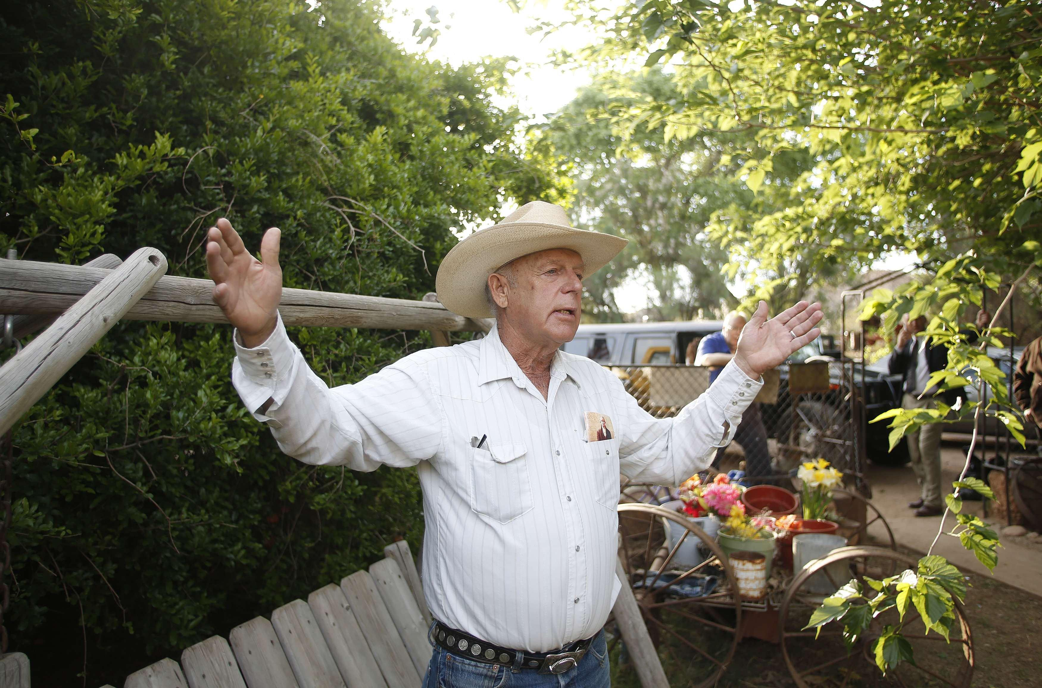 Image: Rancher Cliven Bundy gestures at his home in Bunkerville