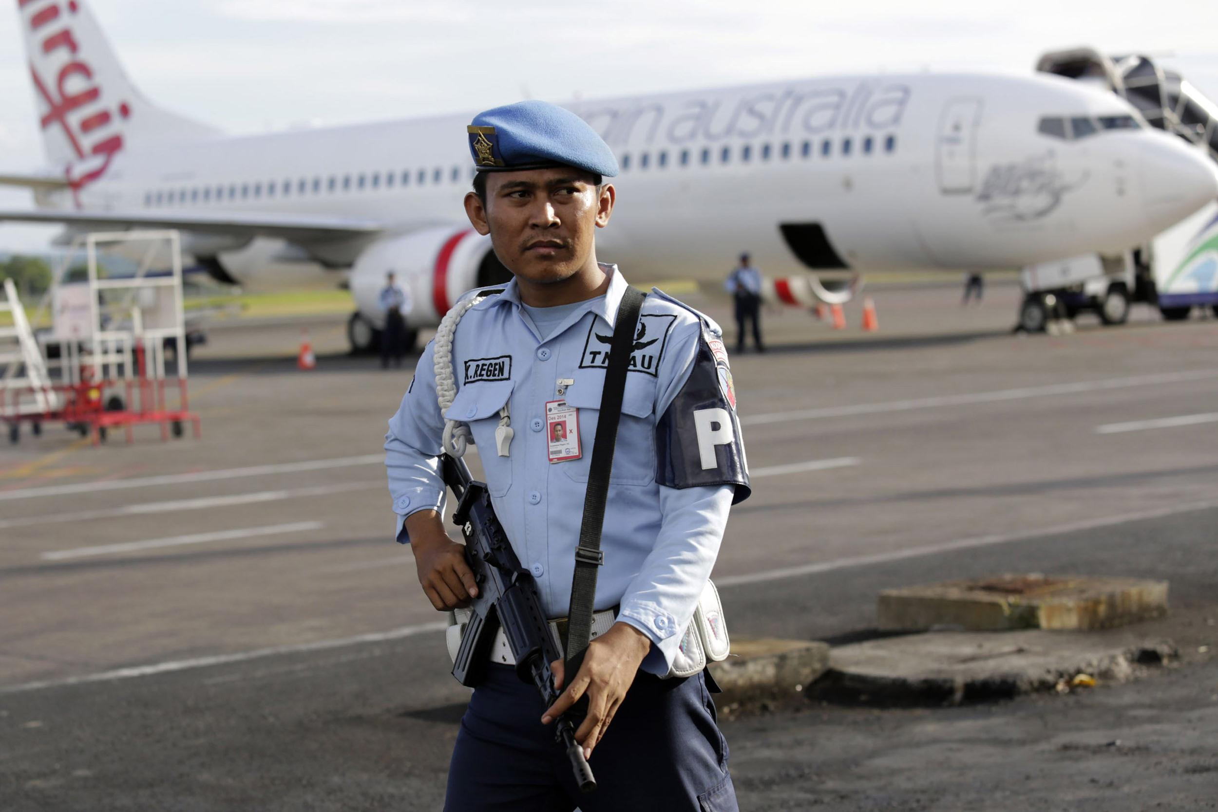 Image: A member of the Indonesian military stands guard near a Virgin Australia plane