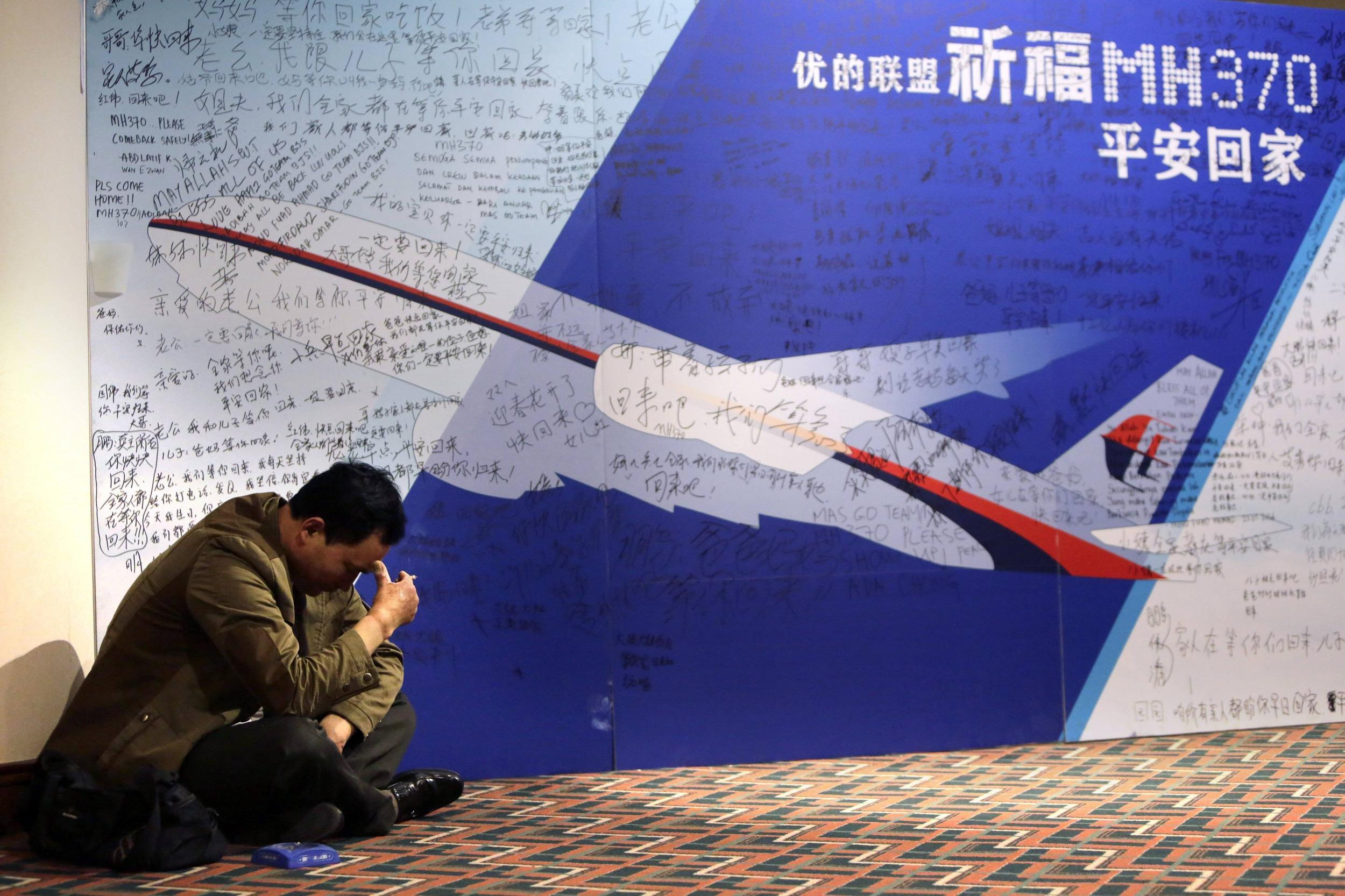 Image:A family member of a Flight 370 passenger sits near message board at Lido Hotel in Beijing on March 29