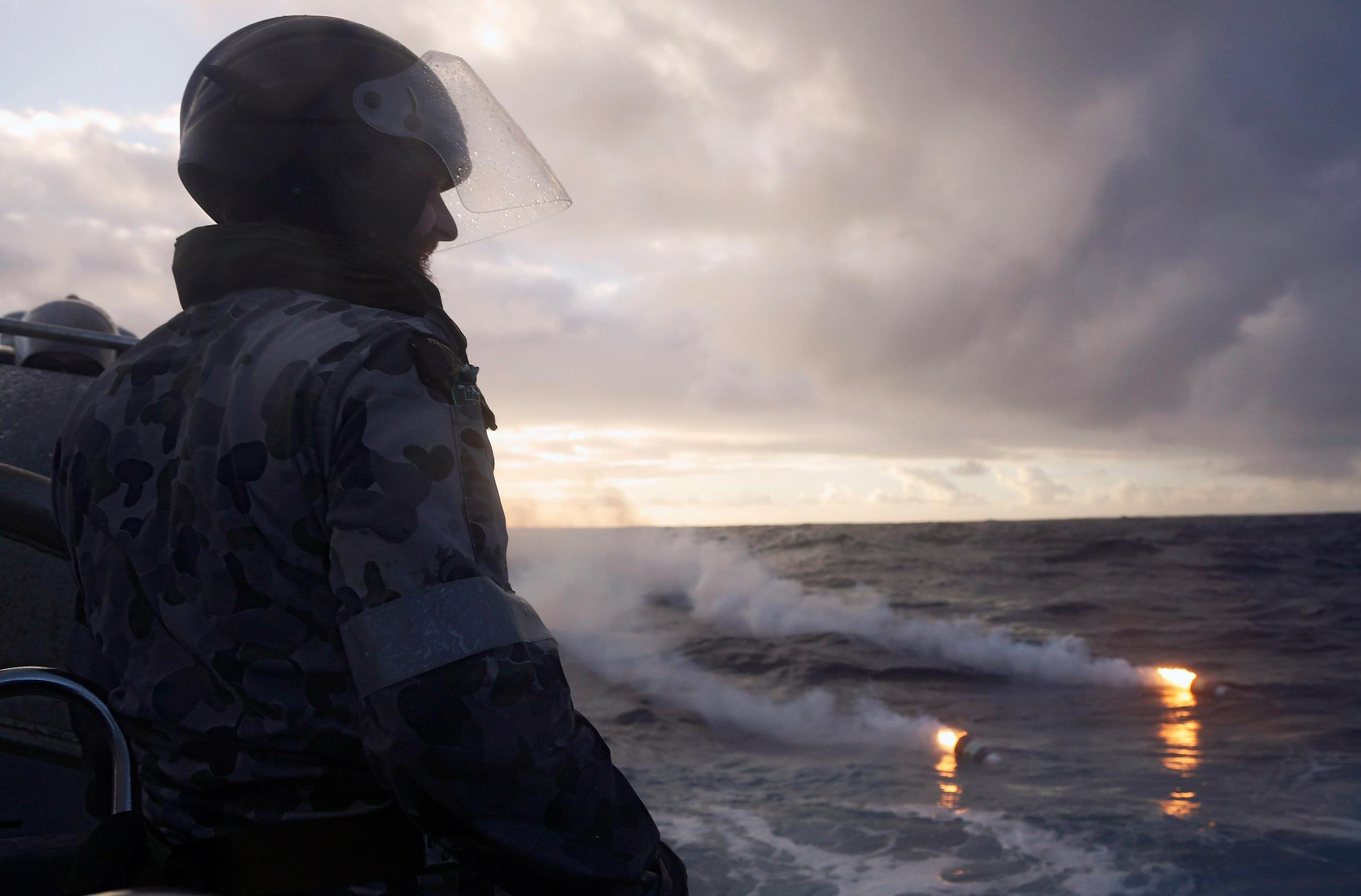 Image: Boatswain's Mate, Able Seaman Morgan Macdonald, observes markers dropped from a RNZAF P3K Orion after an object was sighted in the southern Indian Ocean during the continuing search for the missing Malaysian Airlines flight MH370