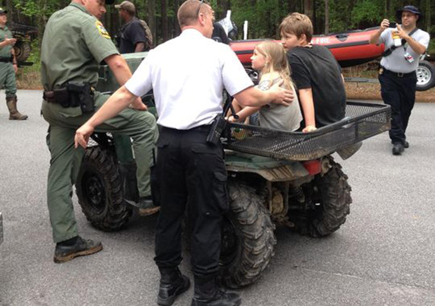 Officials speak with Jade and Dakota Kimbler Tuesday morning after they were rescued in Congaree National Park.