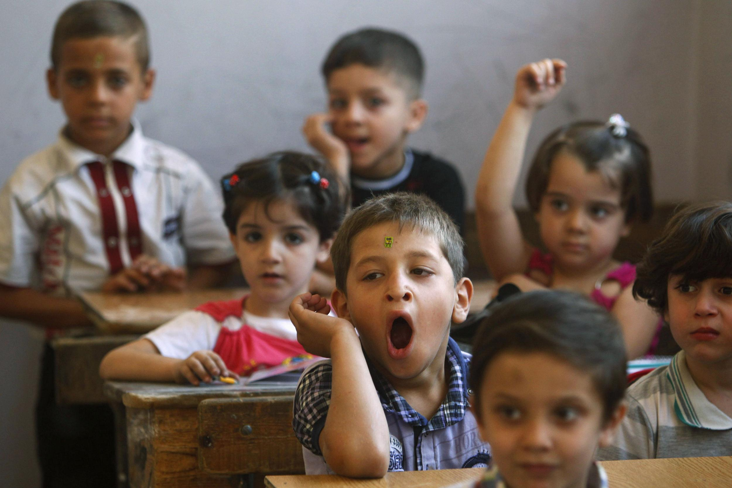Image: A pupil yawns in classroom at start of new school year in the city of Aleppo