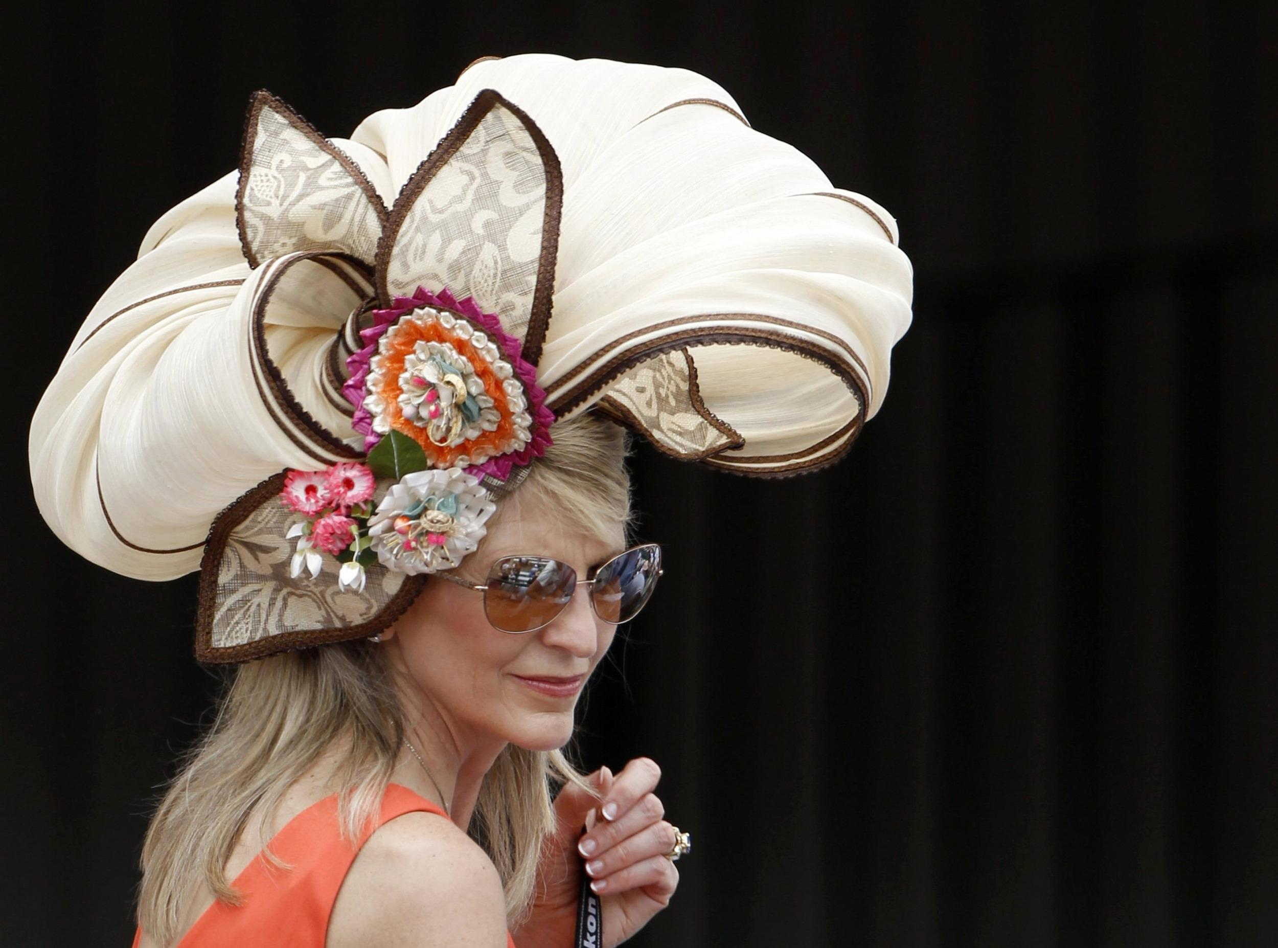 Image: A woman wears a fancy hat before the Kentucky Derby at Churchill Downs in Louisville