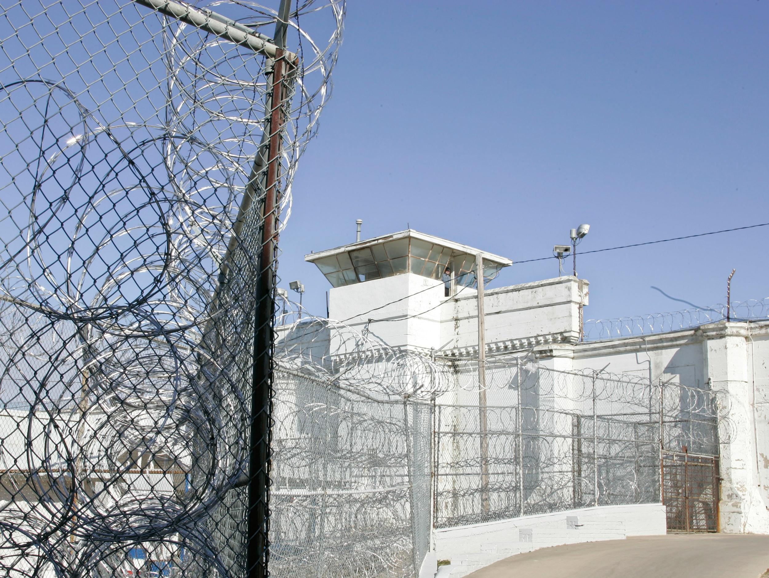 Image: A guard tower and razor wire at the  Oklahoma State Penitentiary in McAlester, Okla.