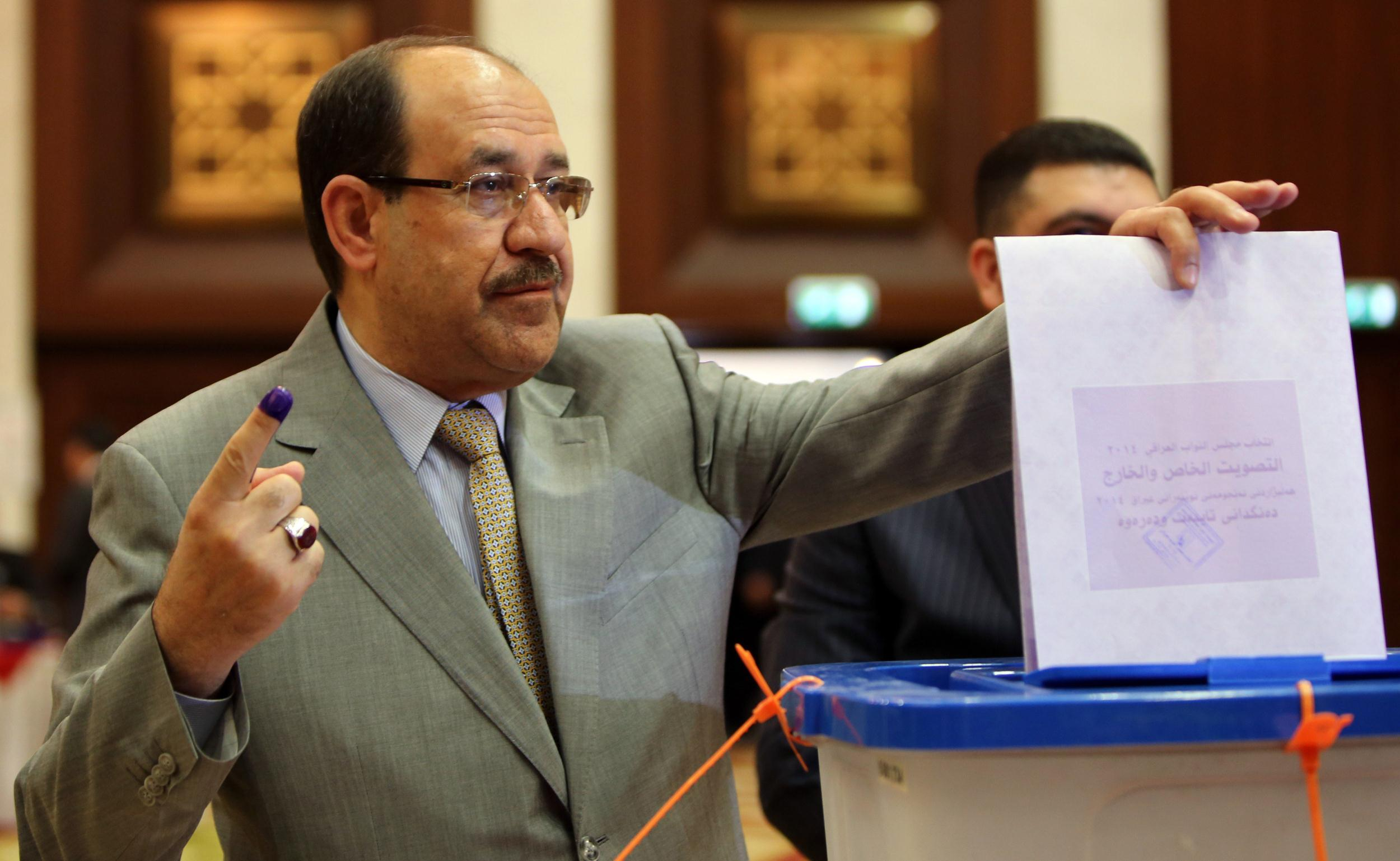 Image: Iraqi Prime Minister Nouri al-Maliki shows his ink-stained finger as he casts his vote