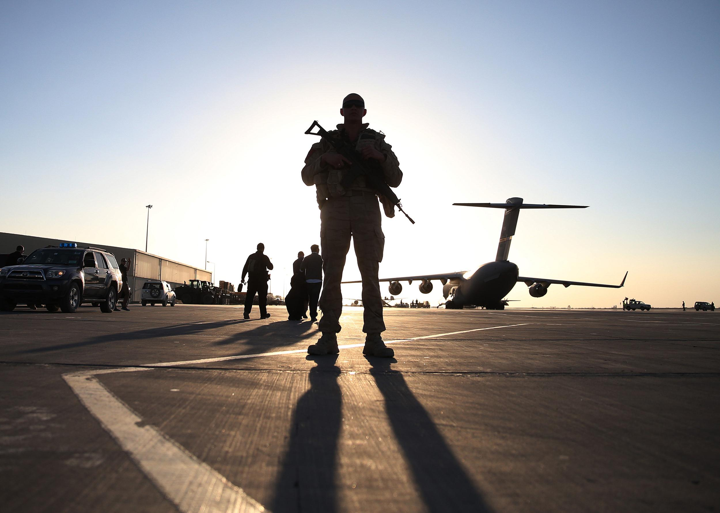 A soldier stands guard near a military aircraft in Kandahar
