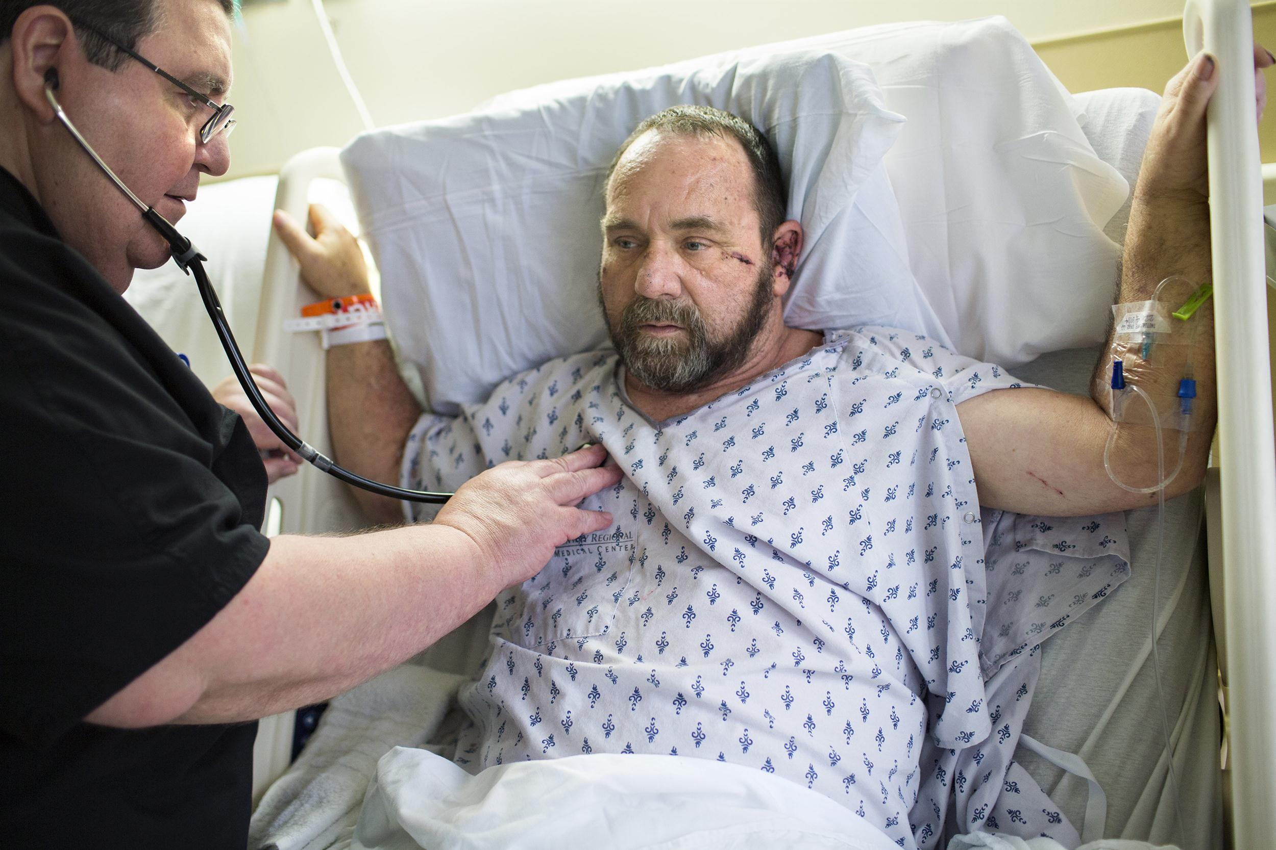 Image: Respiratory therapist Darrell Benham listens to Harold Fowler breathe at Conway Regional Medical Center