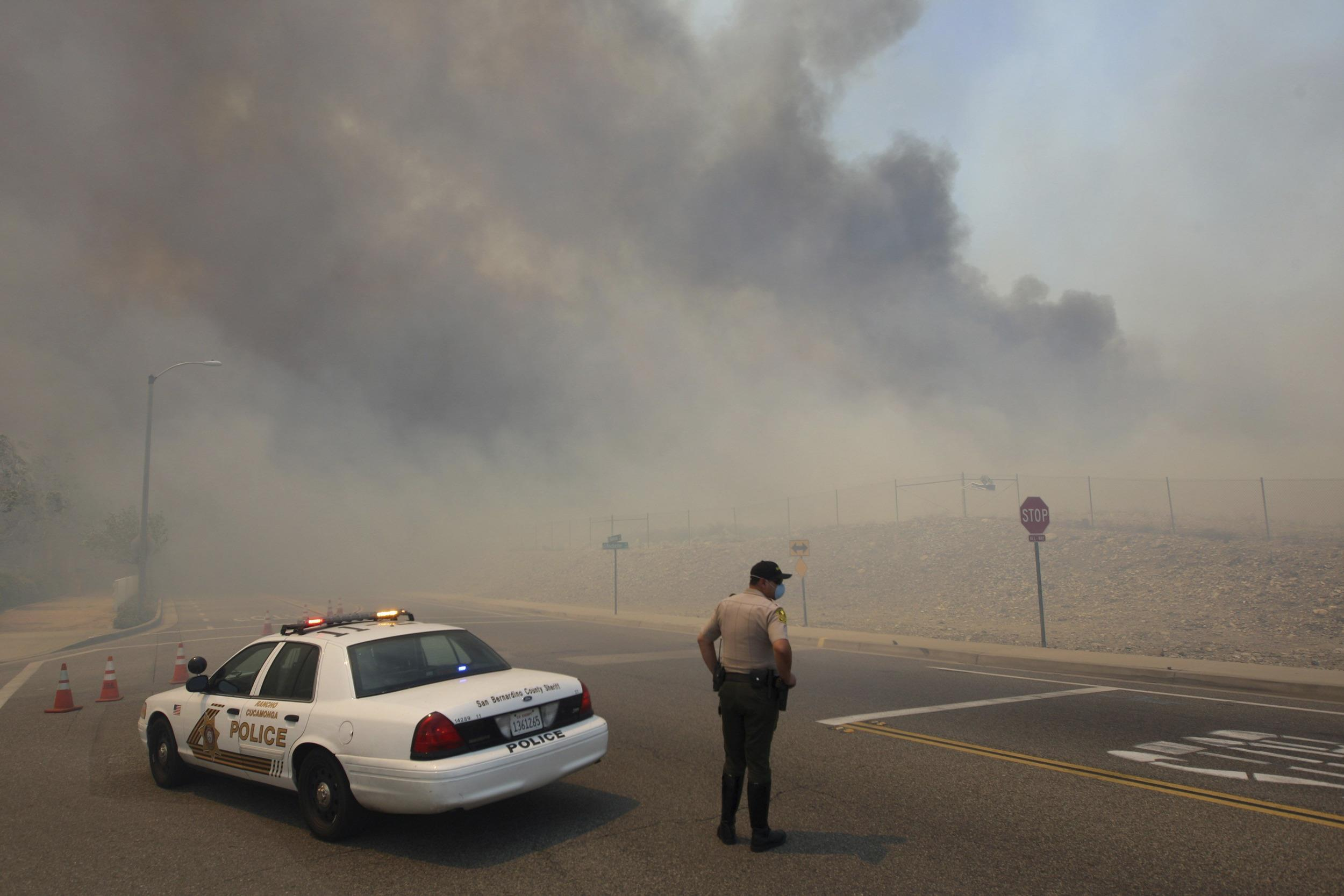 Image: A police officer mans a roadblock as smoke billows from a wildfire driven by fierce Santa Ana winds in Rancho Cucamonga, California