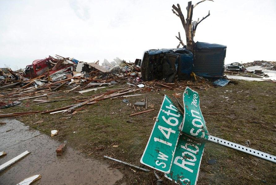 IMAGE: A twisted street sign lay atop wreckage in a destroyed neighborhood in Moore, Okla., after a monster tornado in May 2013.