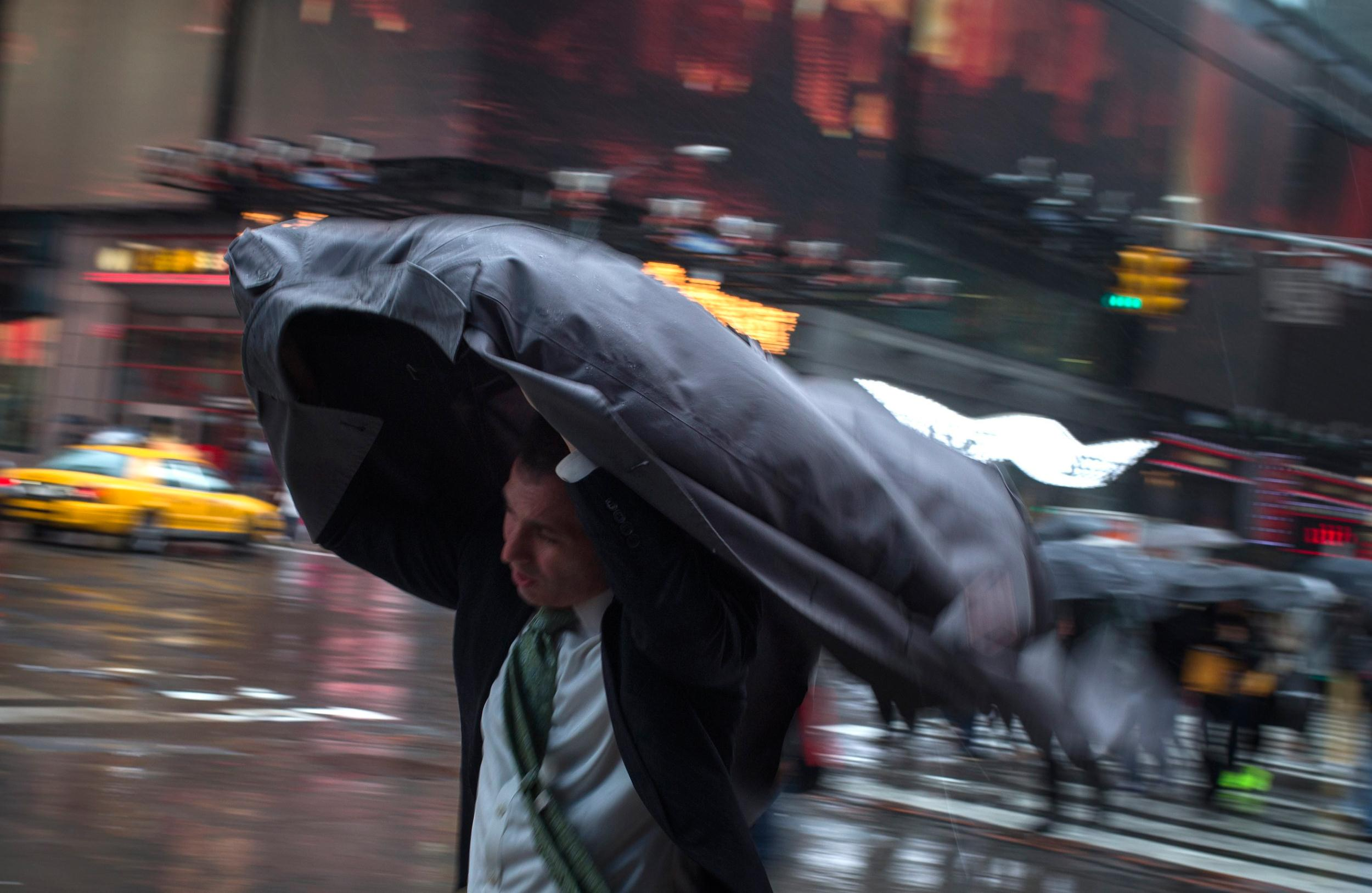Image: A man uses his rain coat to guard against rain and wind as he commutes through Times Square, New York