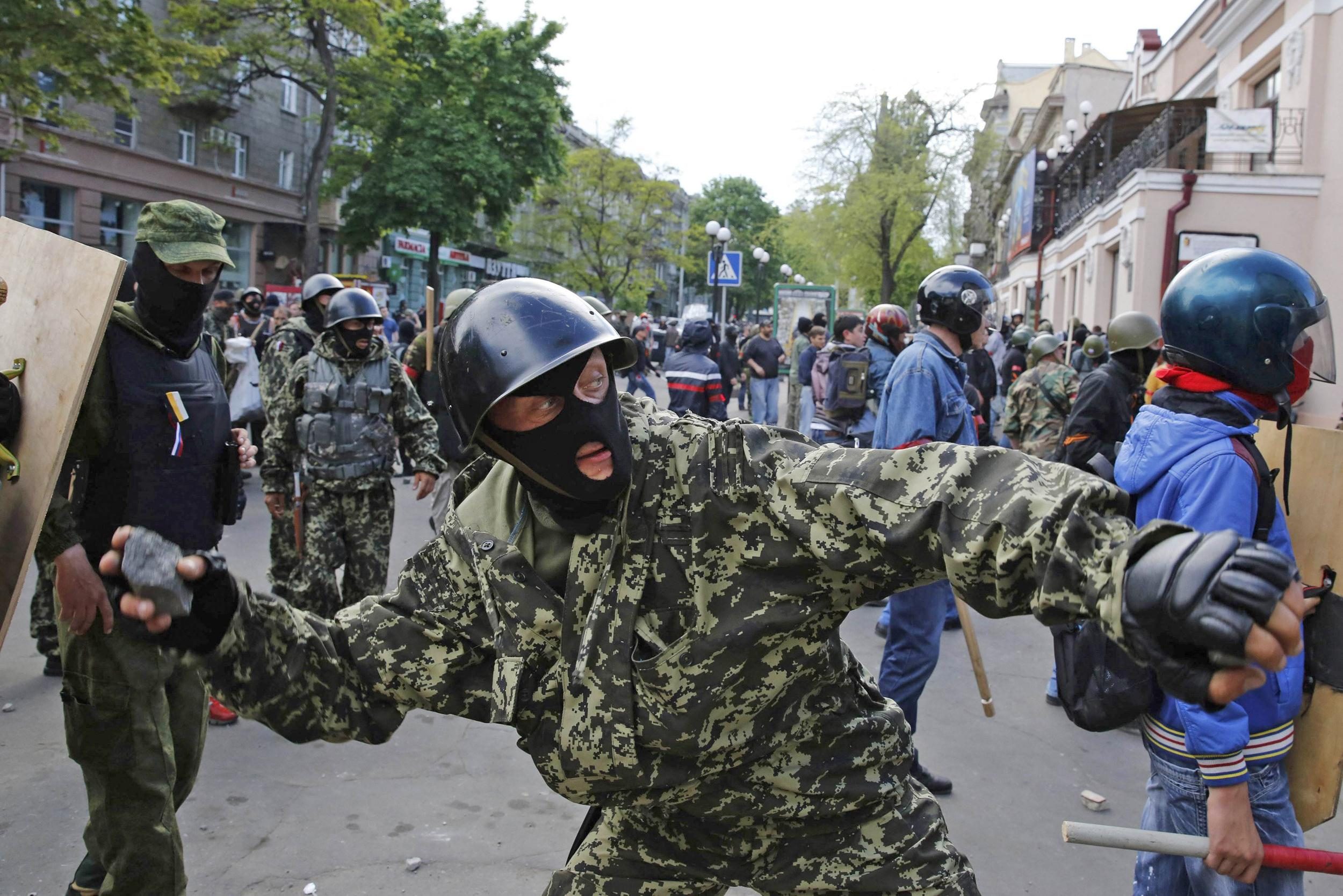 Image: A pro-Russian activist hurls an object at supporters of the Kiev government during clashes in the streets of Odessa