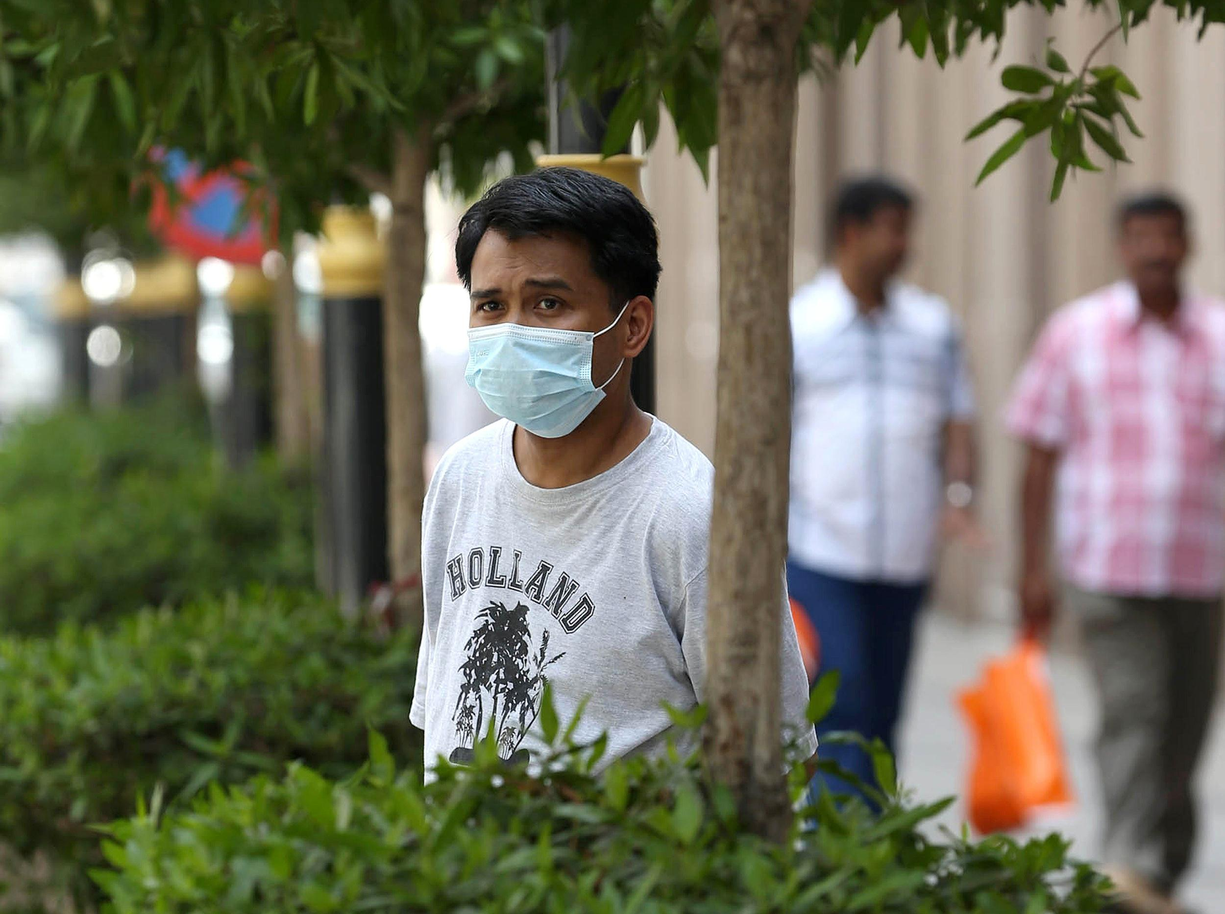 Image: An Asian man wears a mouth and nose mask as he walks in a street of the Red Sea coastal city of Jeddah