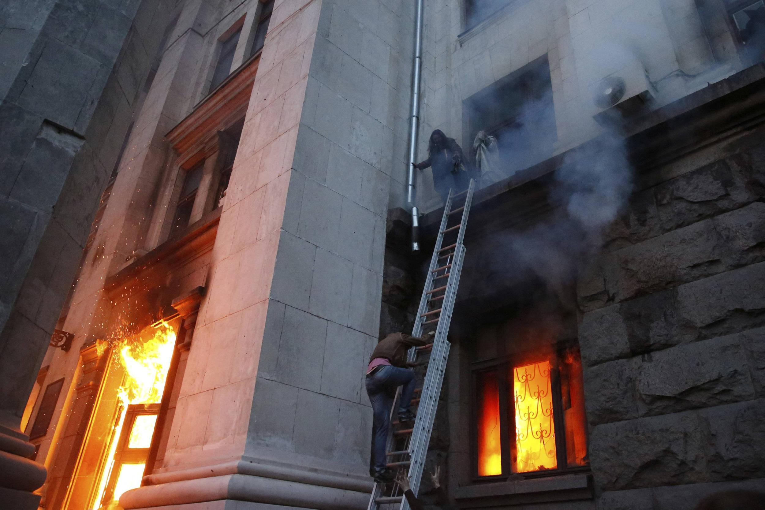 Image: People wait to be rescued on the second storey's ledge during a fire at the trade union building in Odessa