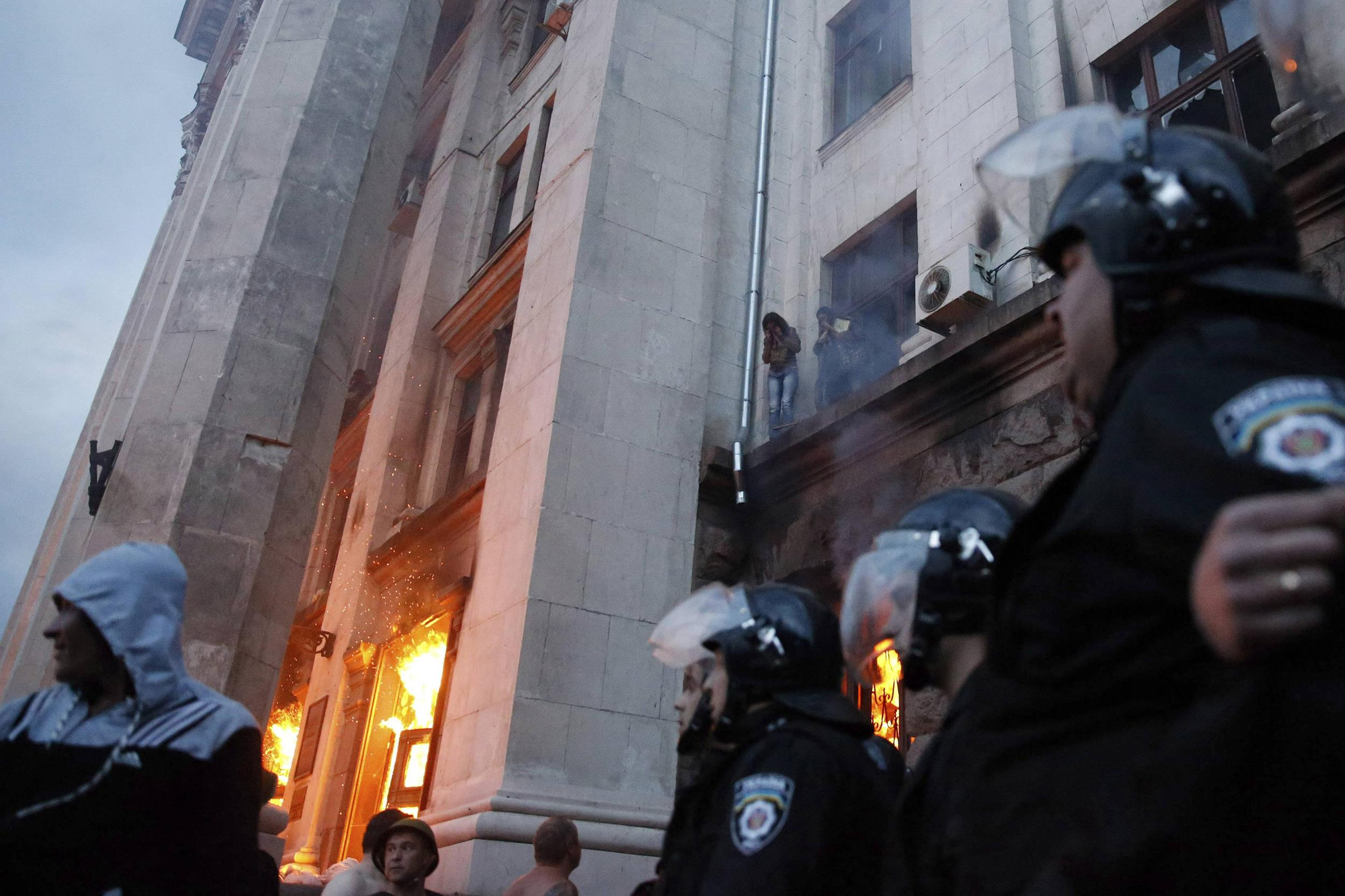 Image: People wait to be rescued on an upper storey ledge during a fire at the trade union building in Odessa