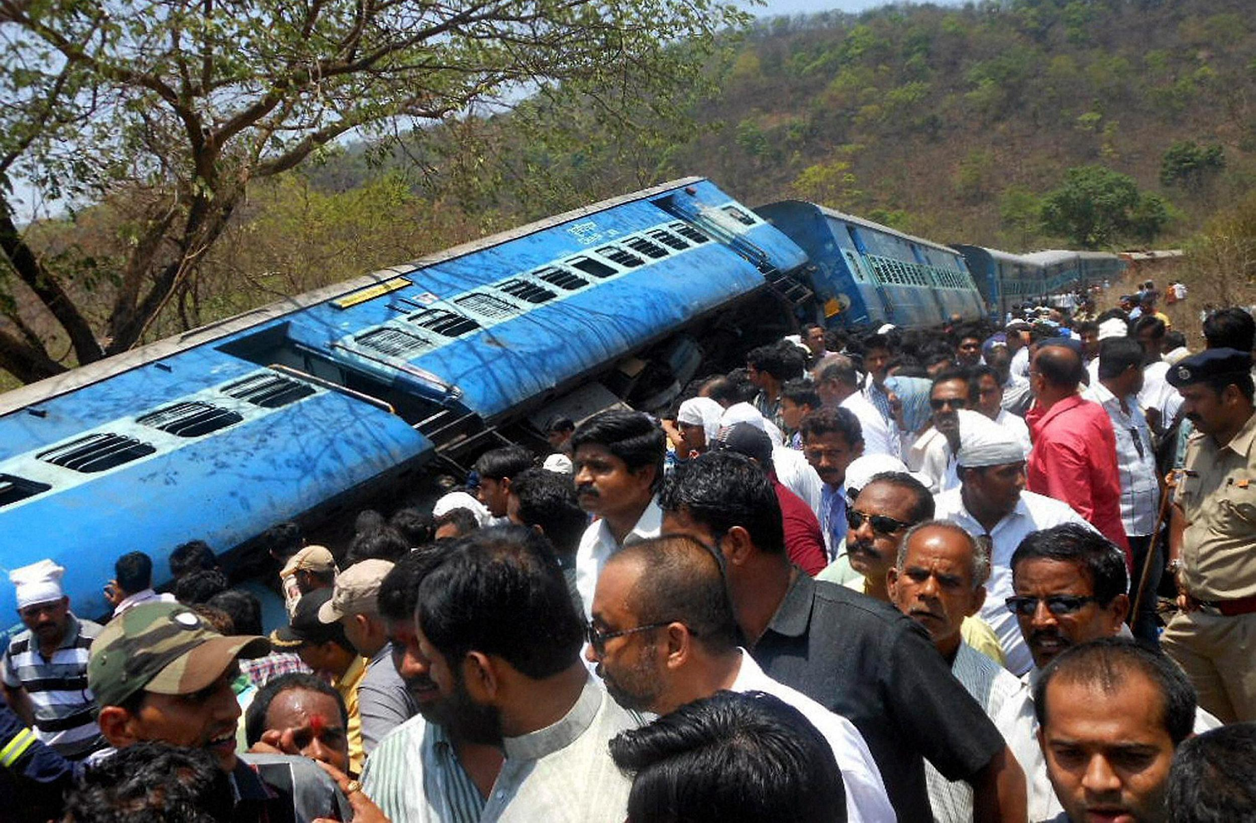 Image: People gather around a passenger train that derailed near Roha station, 70 miles south of Mumbai