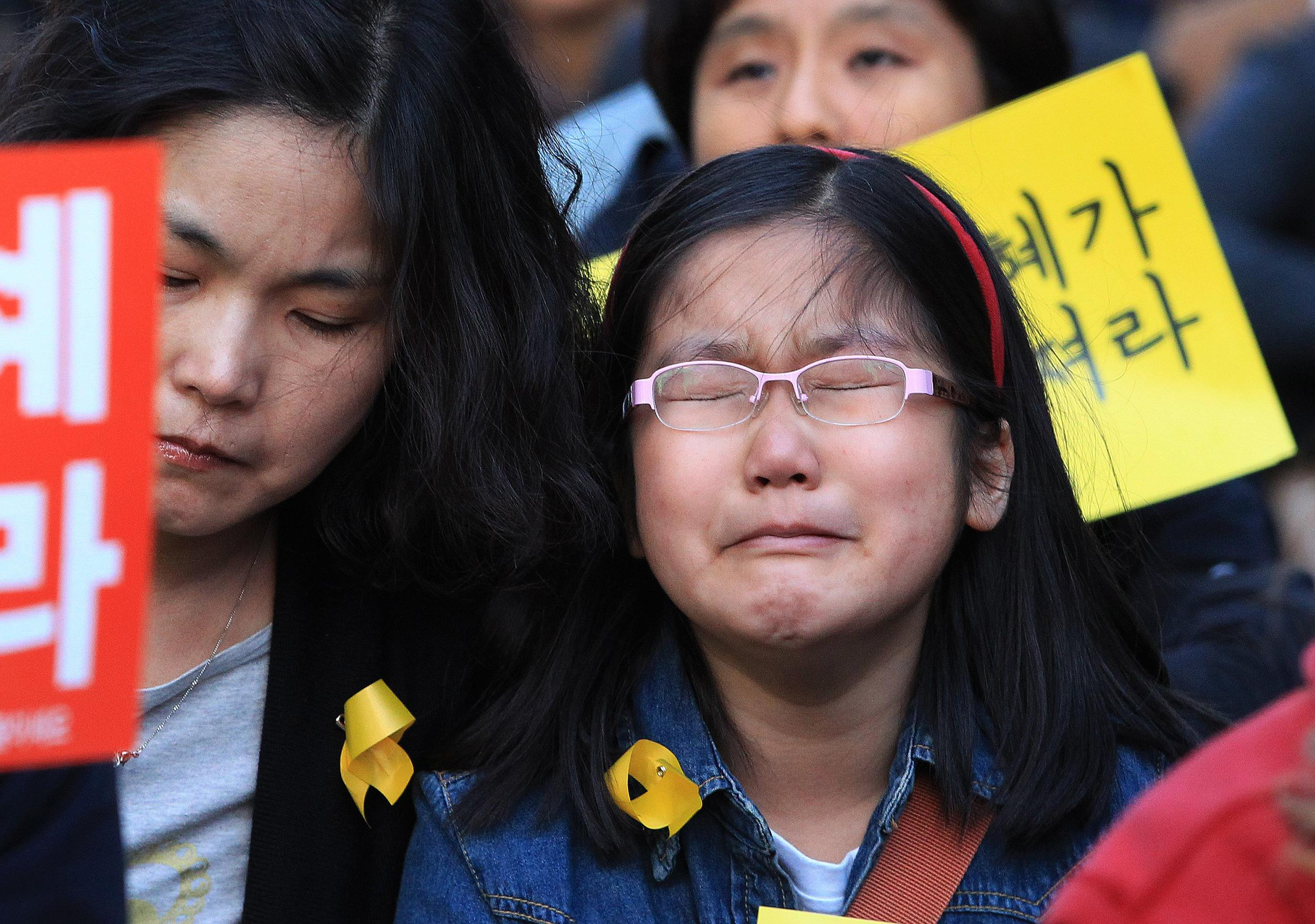 Image: A girl cries during a rally to pay tribute to the victims of the sunken ferry Sewol