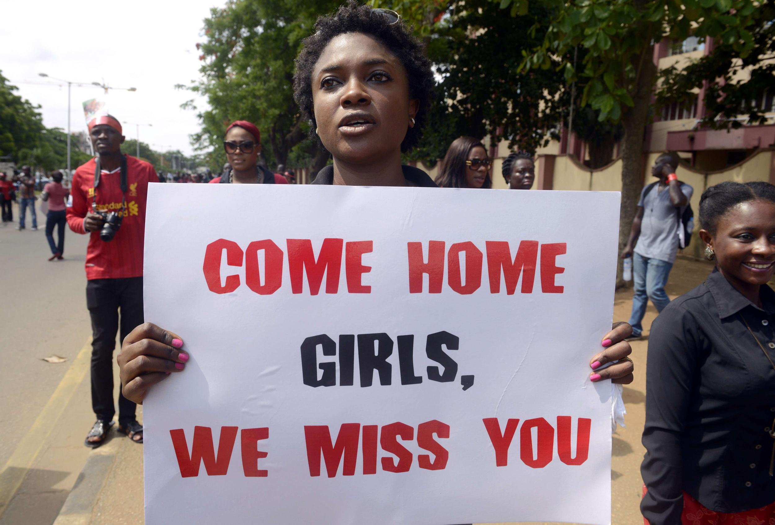 Image: A woman carries placard to press for the release of missing Chibok school girls
