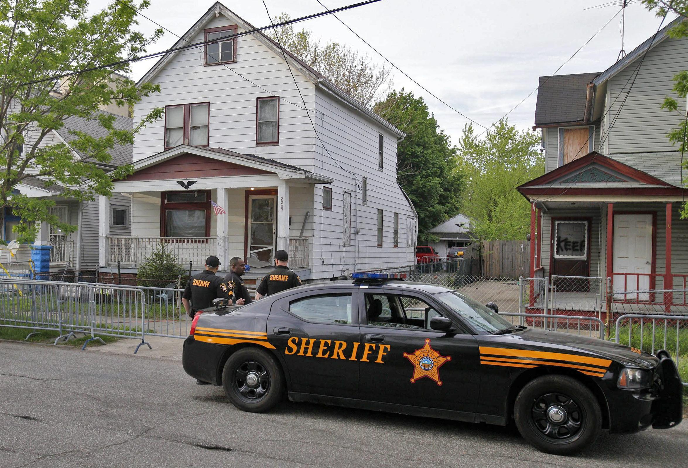 Image: Law enforcement officers stand watch in front of a house on Seymour Avenue in Cleveland, where Amanda Berry, Gina DeJesus and Michelle Knight were found.
