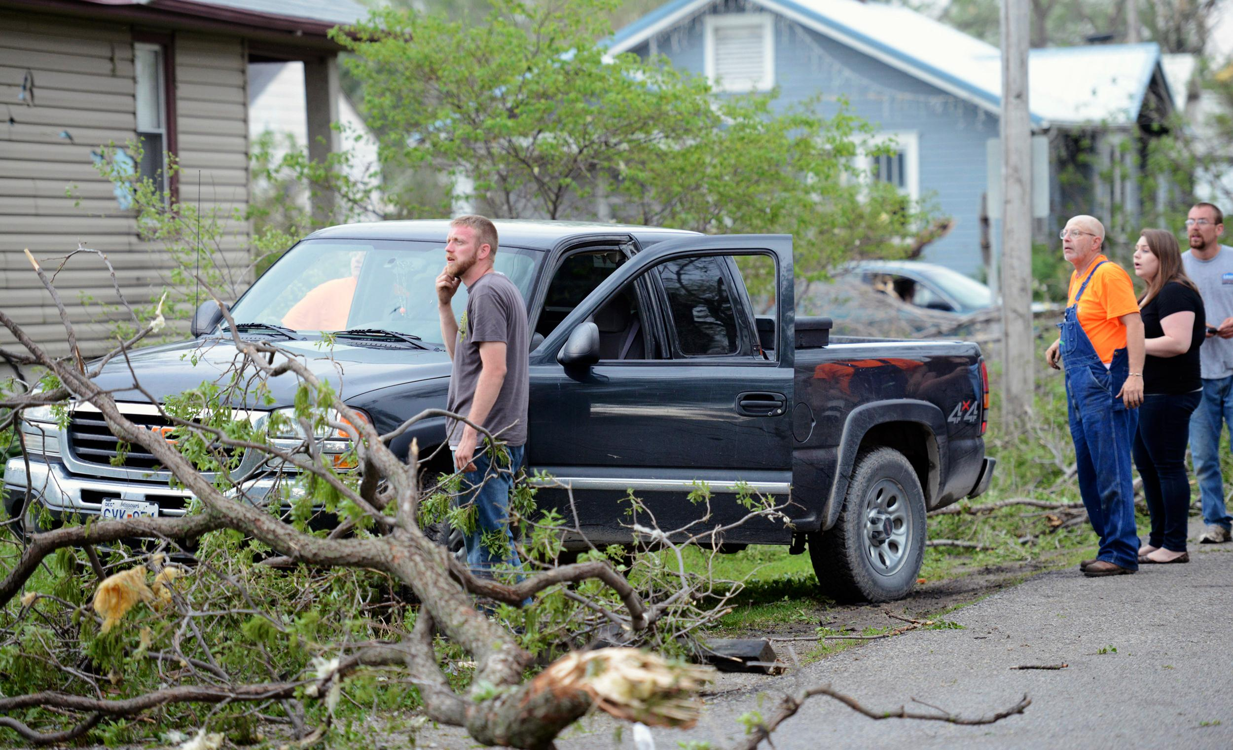 Image: Orrick residents look at the damage after a storm damaged hundreds of homes