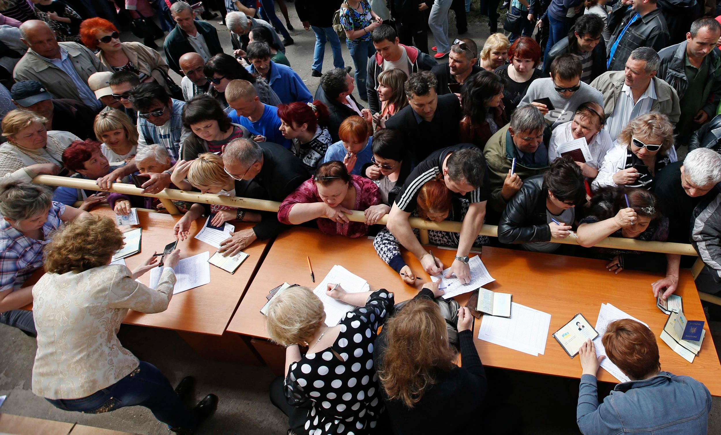 Image: People stand in a line to receive ballots from members of a local election commission during the referendum on the status of Donetsk region in the eastern Ukrainian city of Mariupol