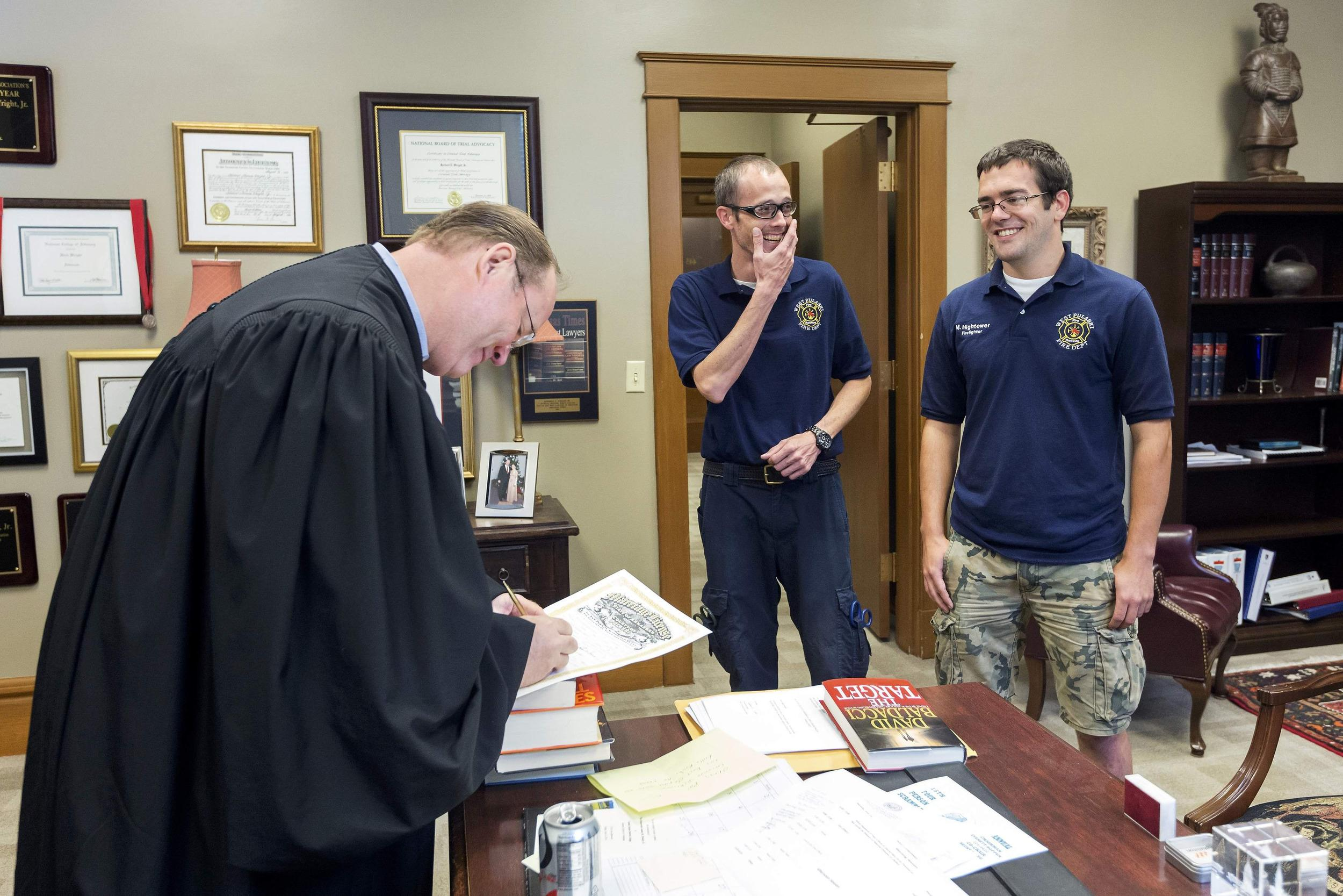 Image: Judge Herbert Wright signs the marriage license of Steven Gibson and Mark Hightower in the Judges chambers at the Pulaski County Courthouse in Little Rock