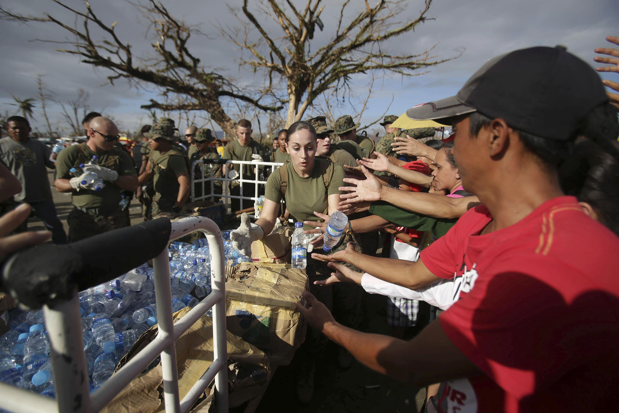 Image: U.S. Marines hand out bottled water to typhoon survivors waiting for flight out of Tacloban city,