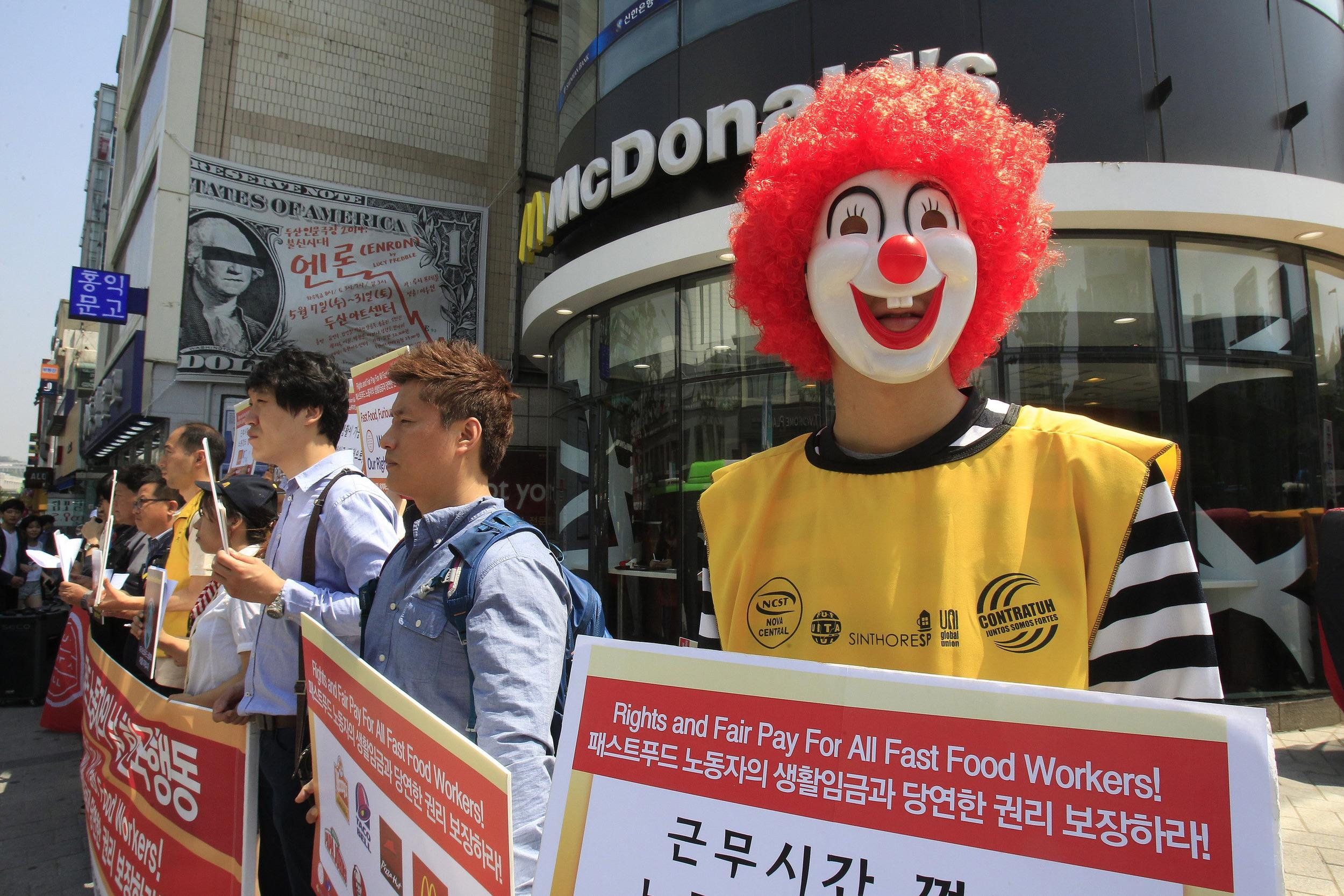A protester dressed as Ronald McDonald participates in a rally to demand higher wages for fast-food workers outside a McDonald's restaurant in Seoul, South Korea.
