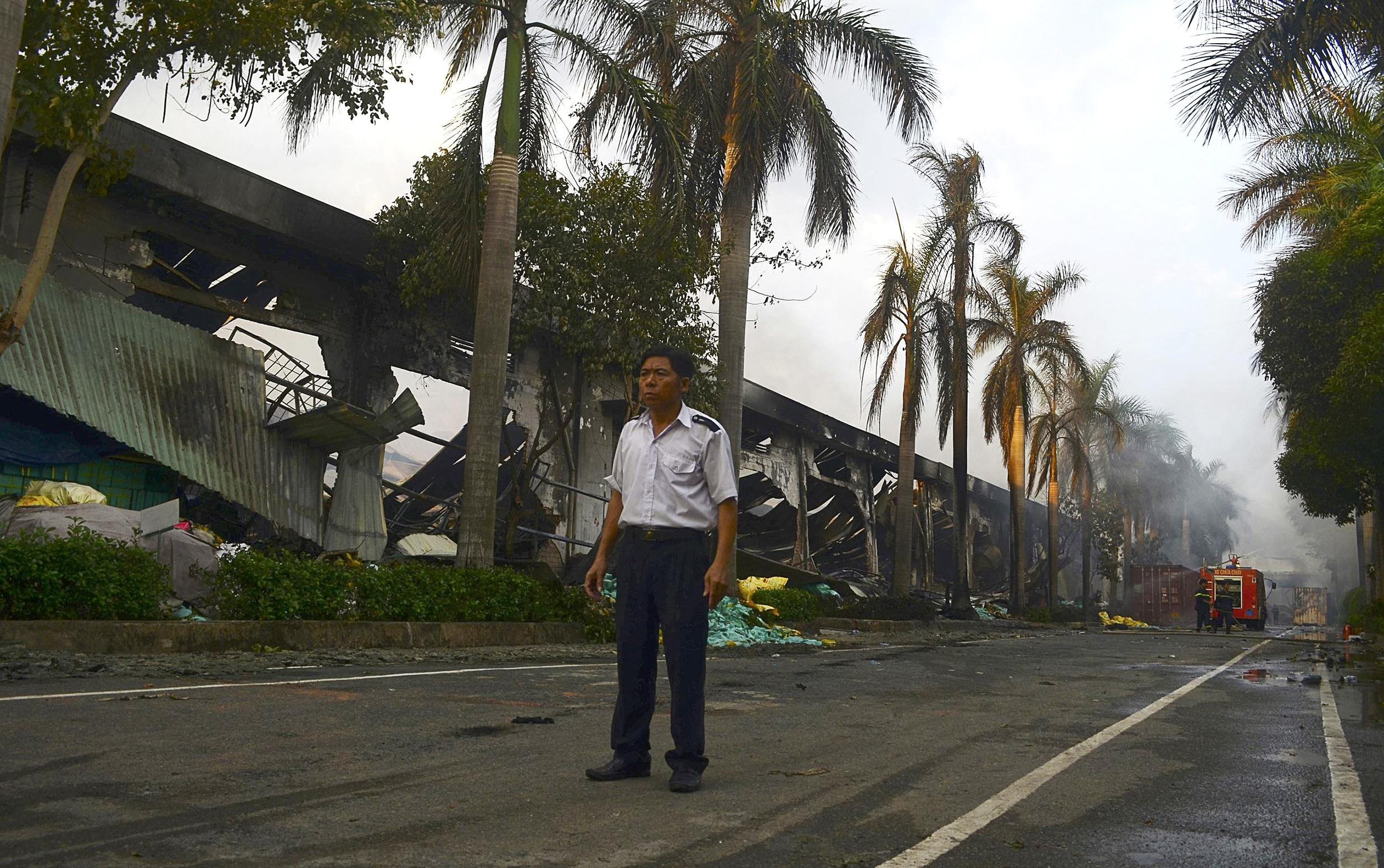 Image: A security guard stands near a damaged Chinese owned shoe factory in Vietnam's southern Binh Duong province