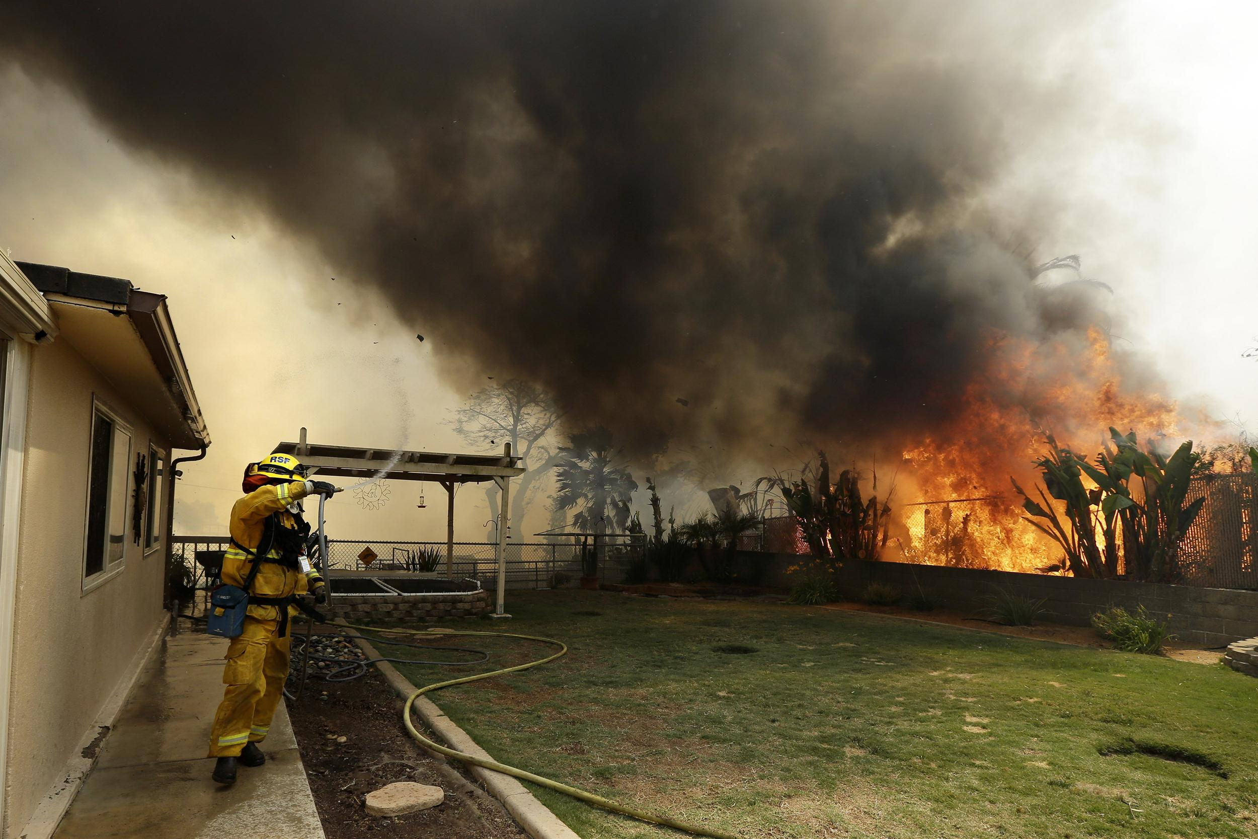 Image: A Riverside firefighter moves away as shifting winds bring a plume of smoke overhead during a wildfire